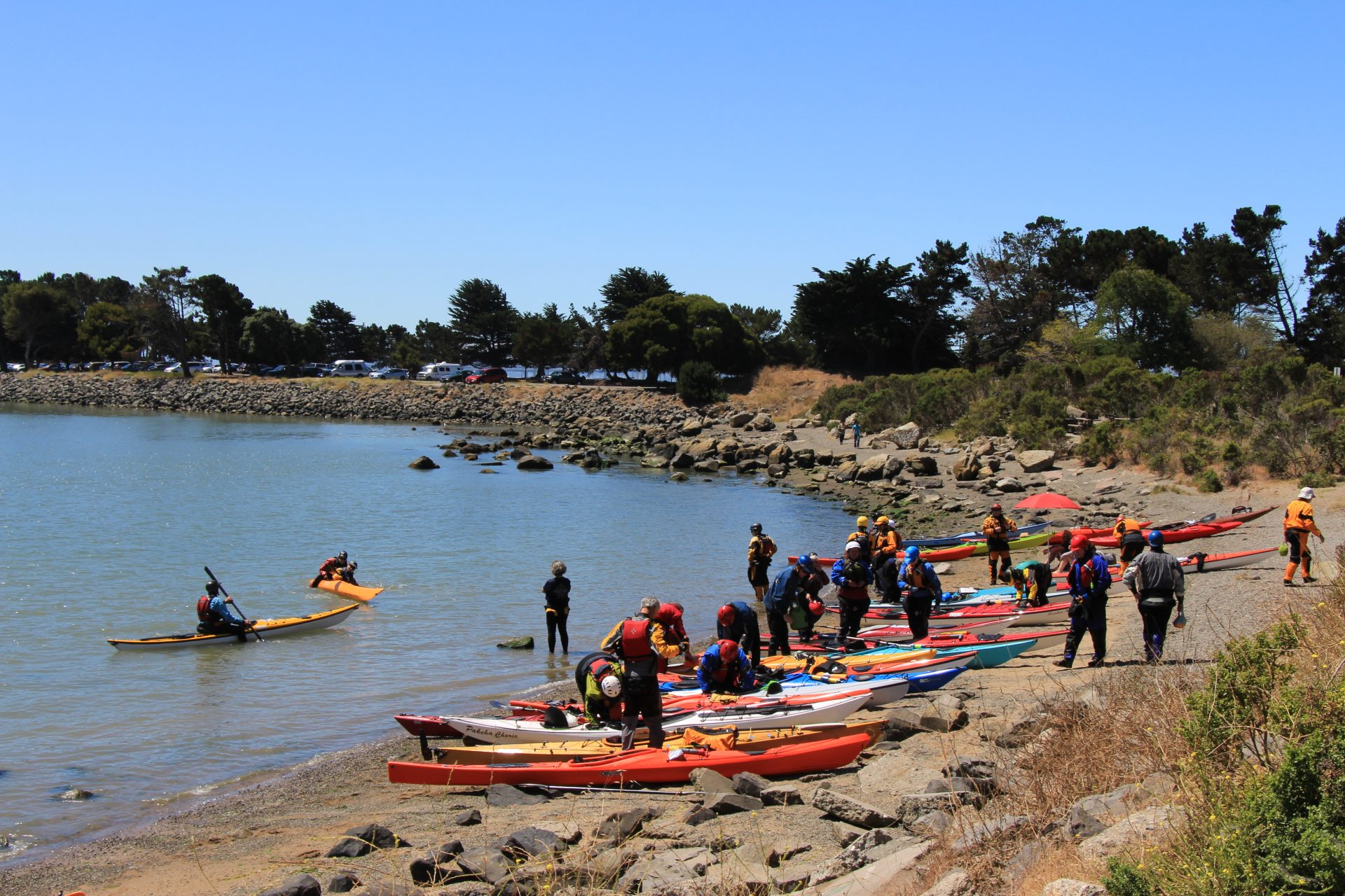 Large group of kayakers milling around boats on sandy beach