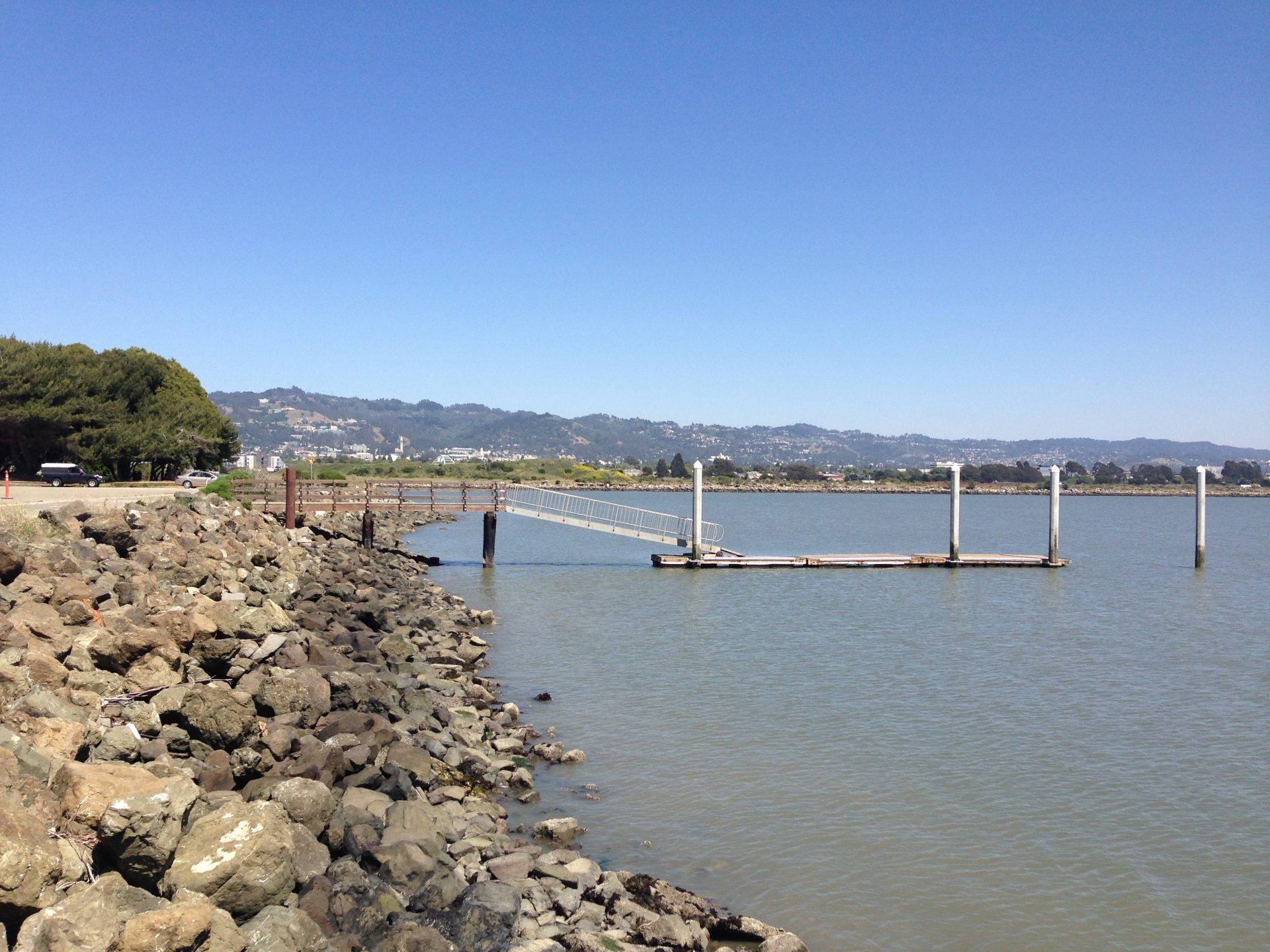 Looking up riprap covered shoreline to wooden pier and ramp down to floating dock