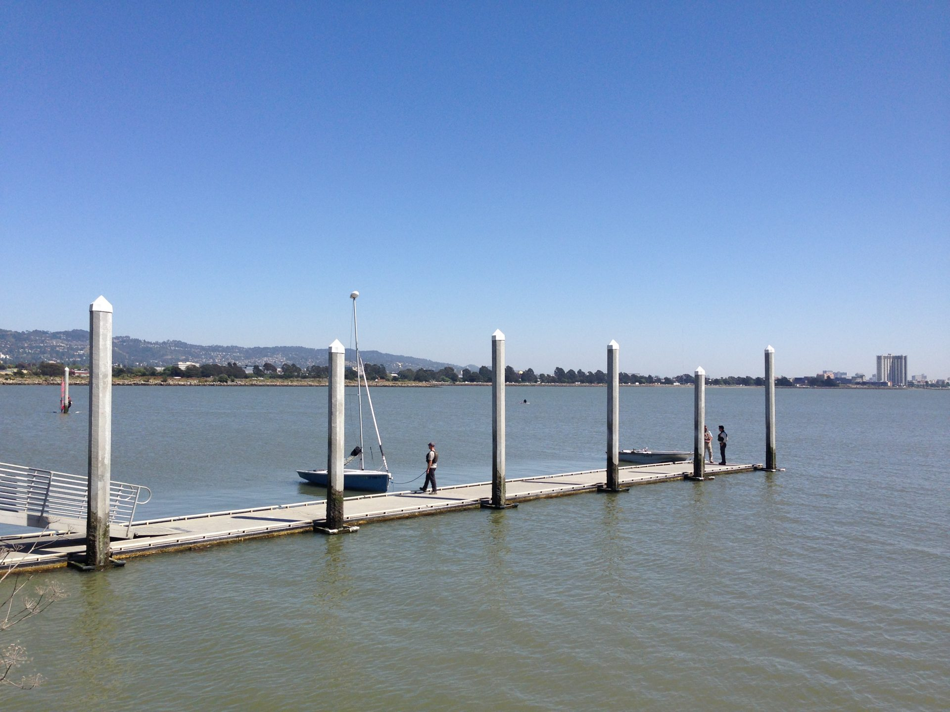 Person mooring small sailboat on flat floating dock
