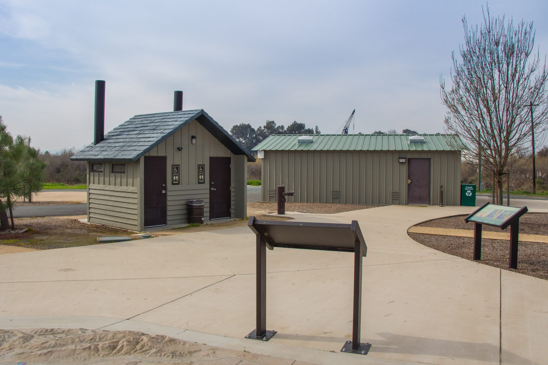 paved area with interpretive panels, bathrooms and shed
