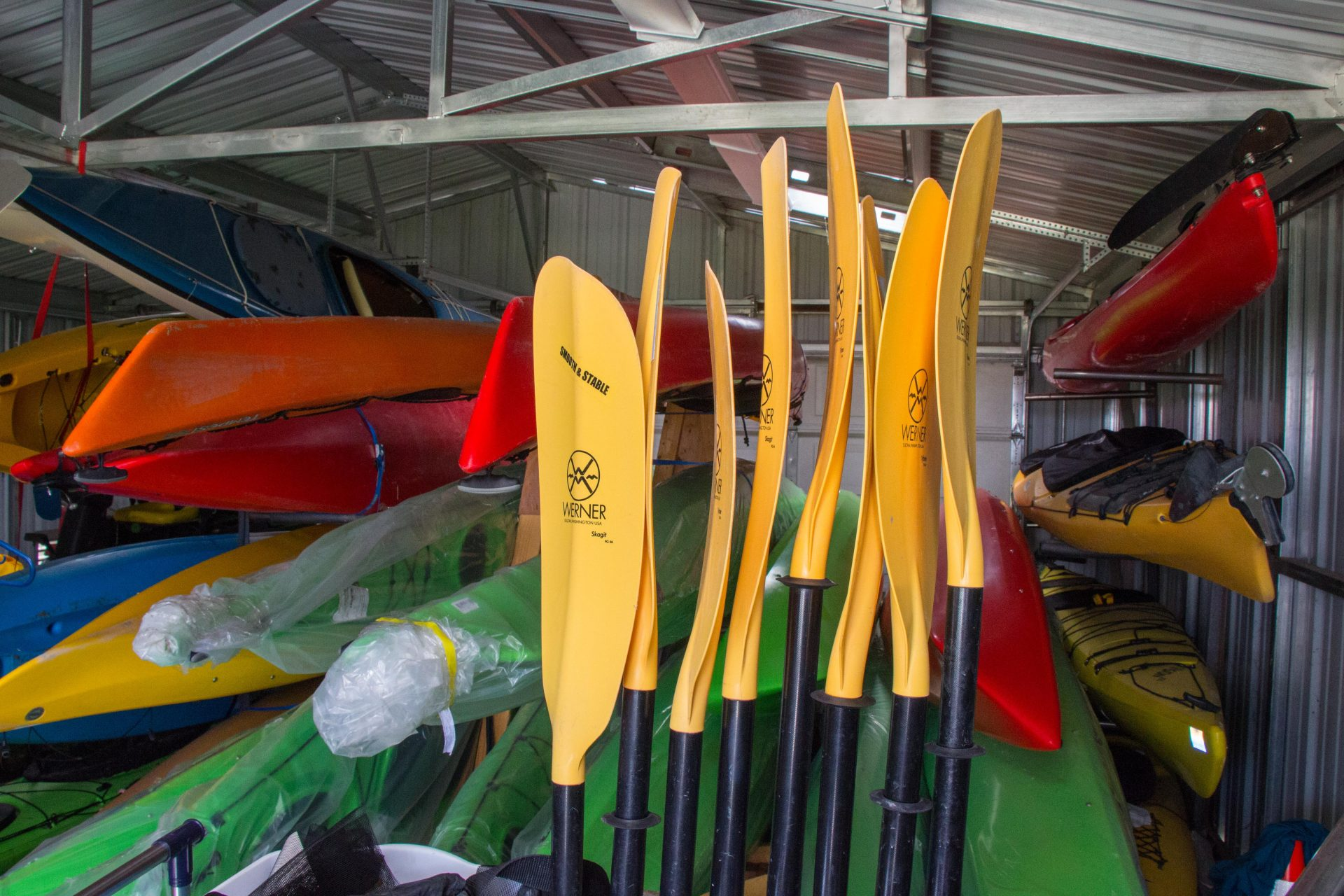 yellow paddles and kayaks in shed