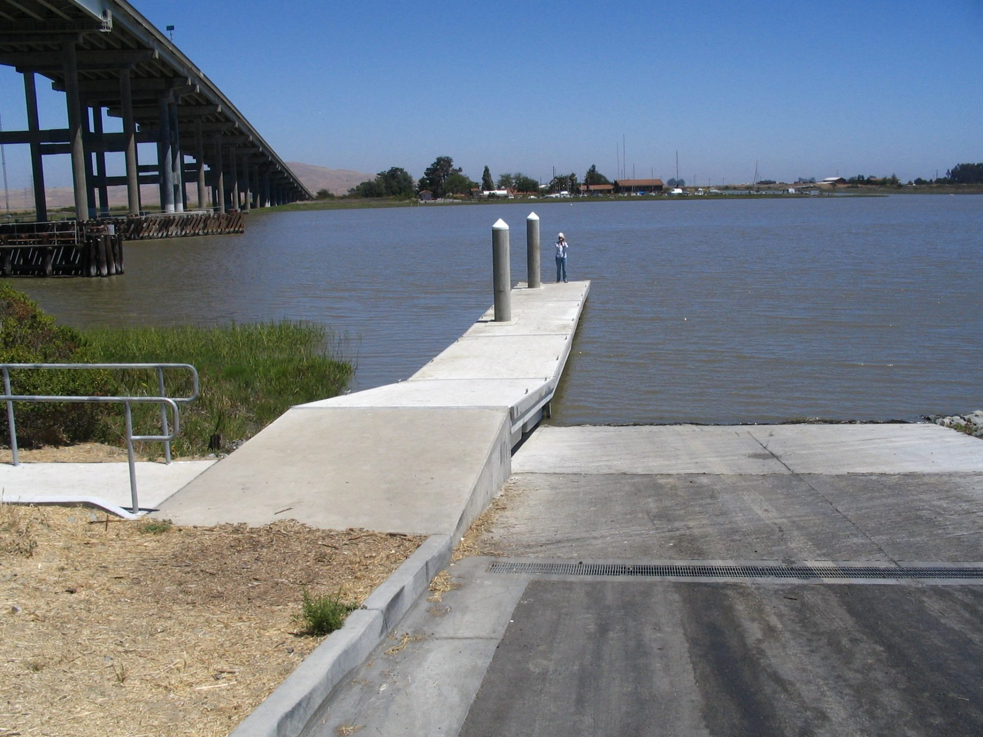 person standing on end of floating dock, next to boat ramp