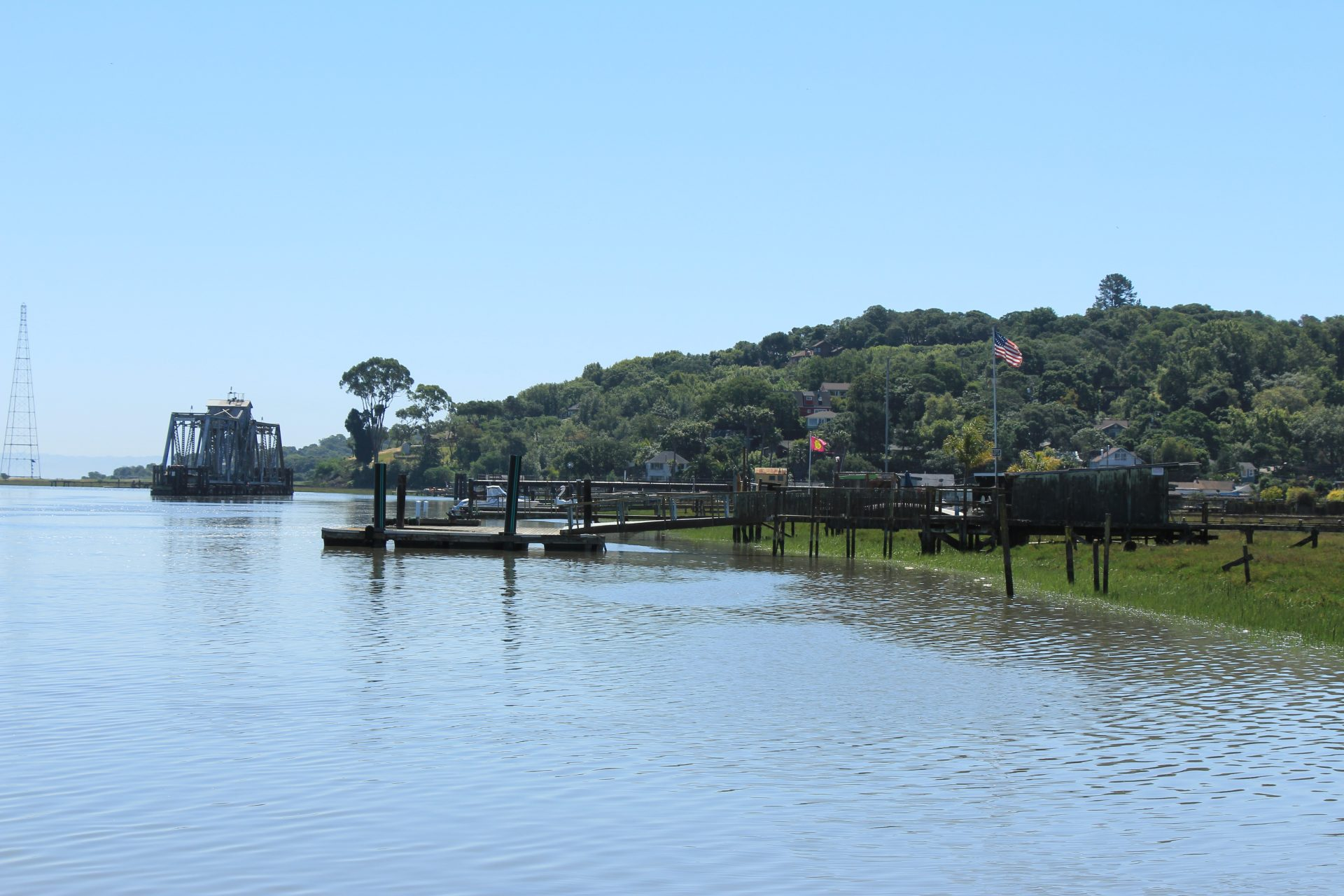 Water, pier and dock structure, forested hill in distance