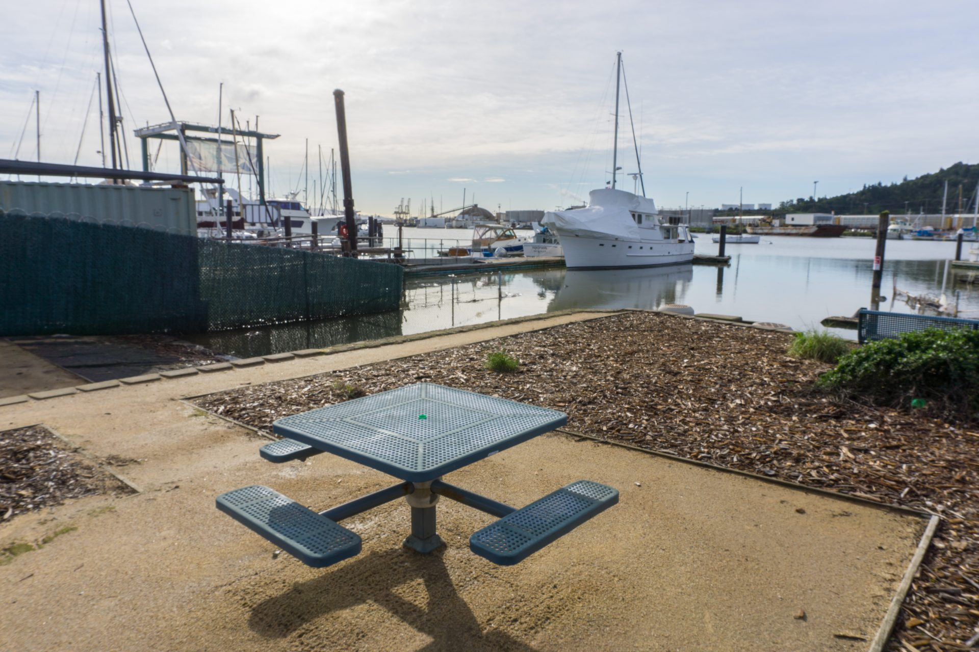 Metal picnic table foreground, boat ramp, and moored sailboats beyond