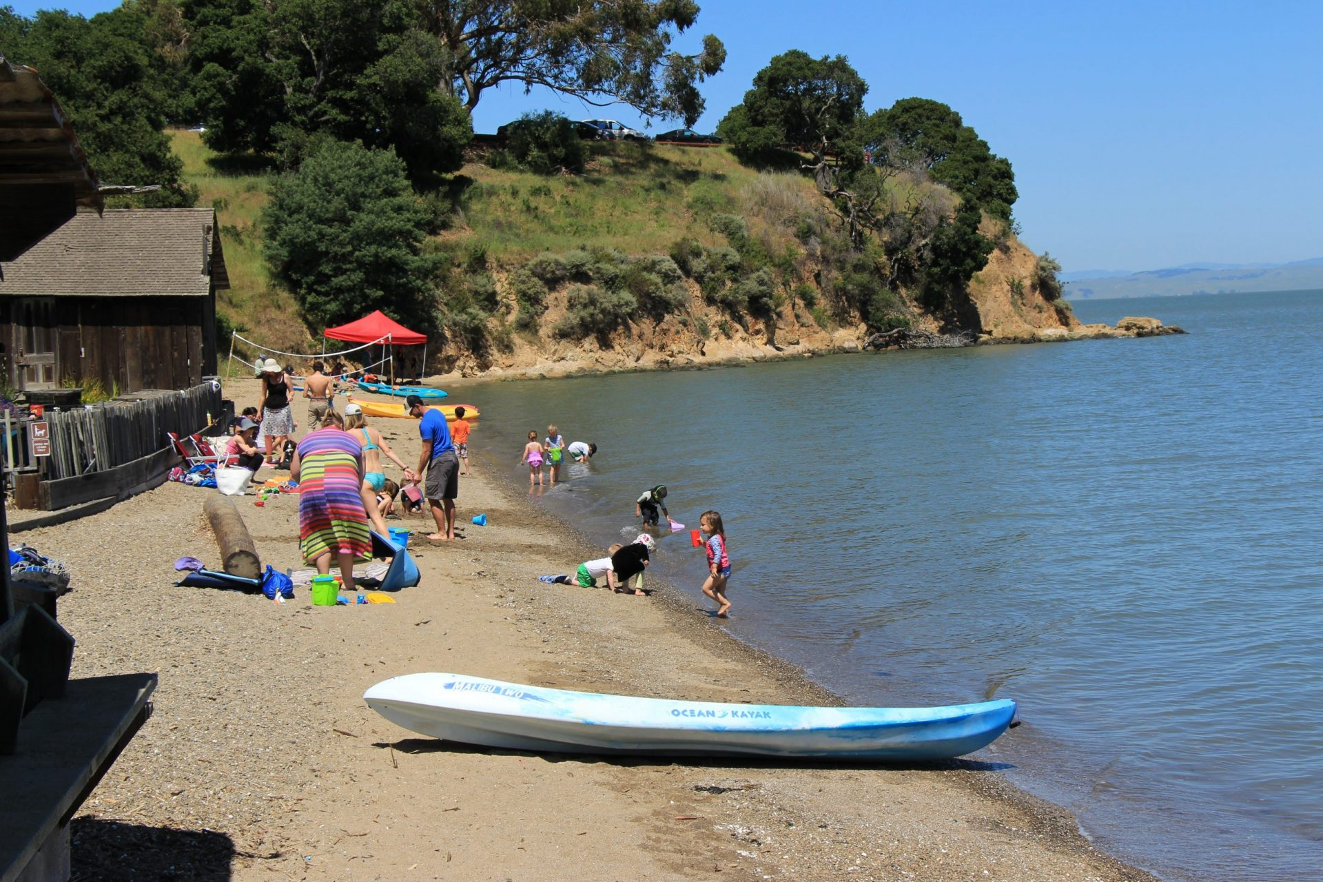 children and adults on narrow beach with kayak in foreground