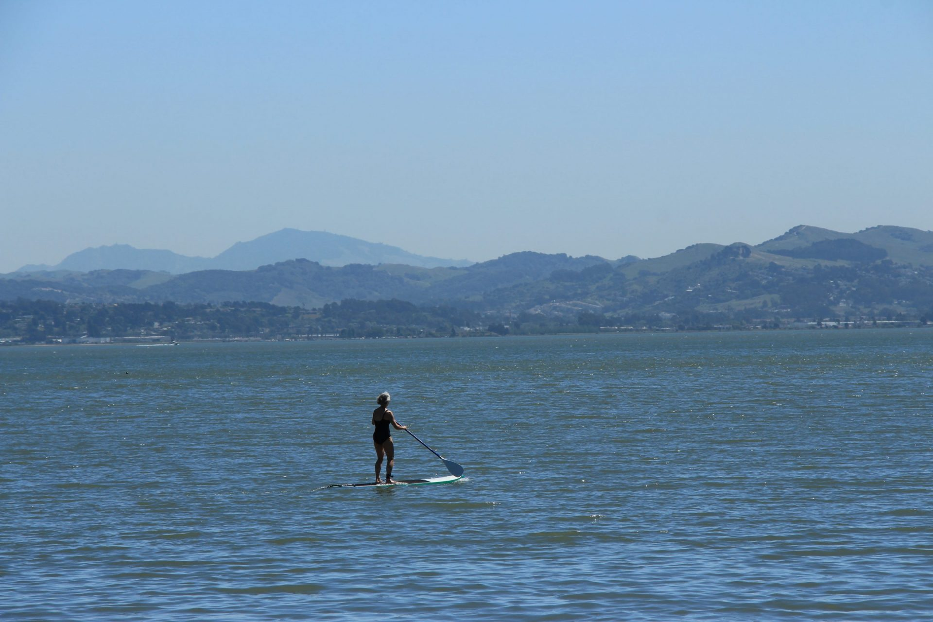 standup paddler on the ater with hills in the distance
