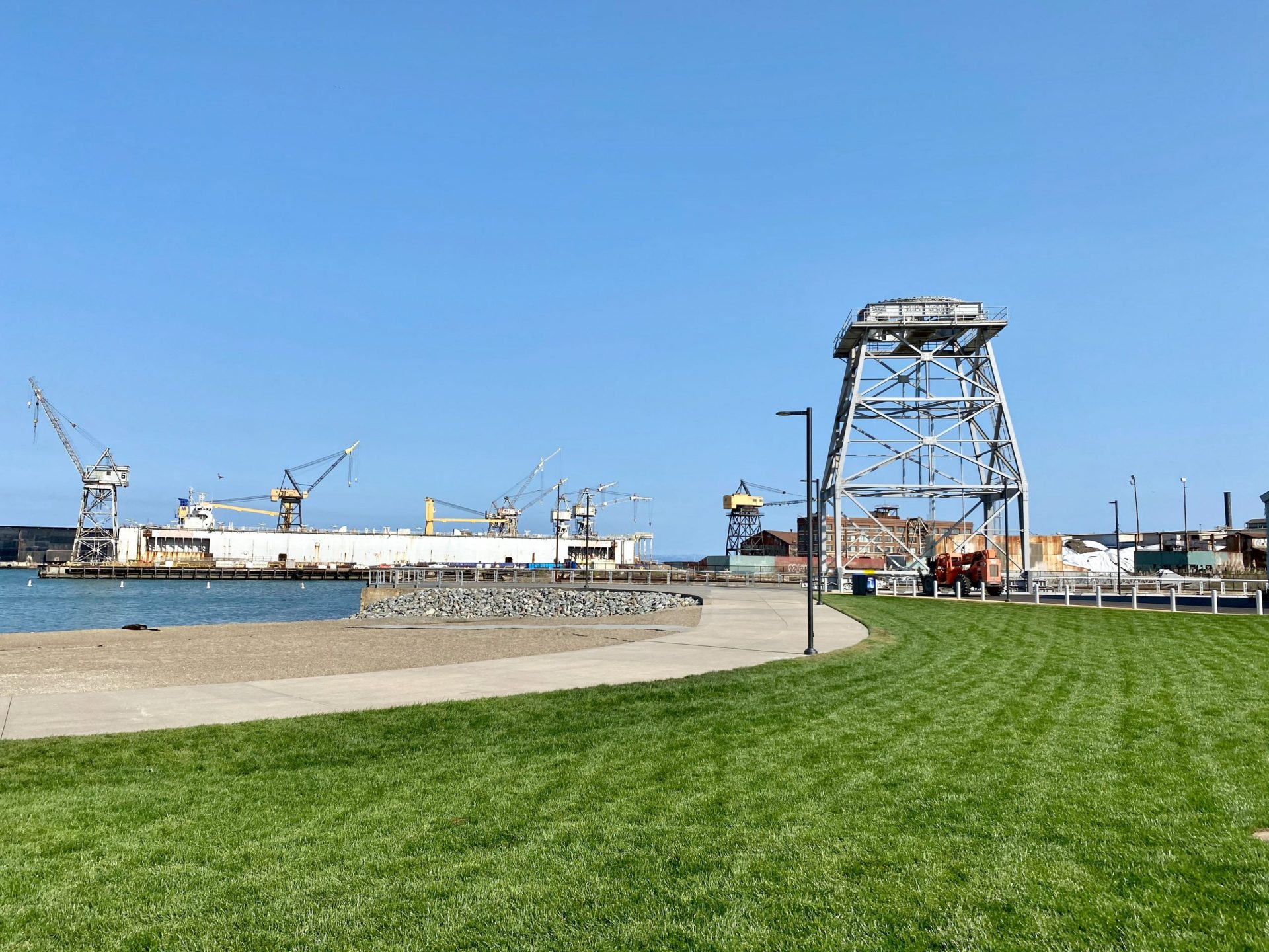 green lawn and beach with crane structure beyond
