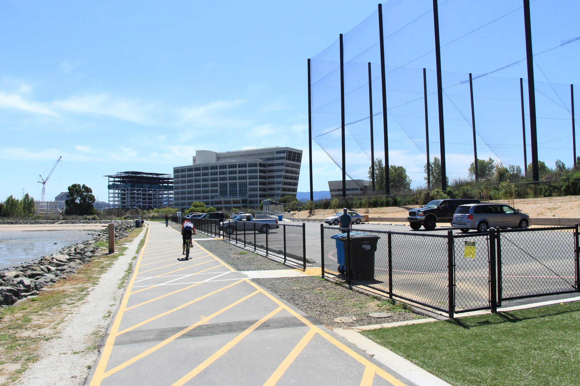 Bicyclist on path alongside fence, with parking lot and driving range beyond