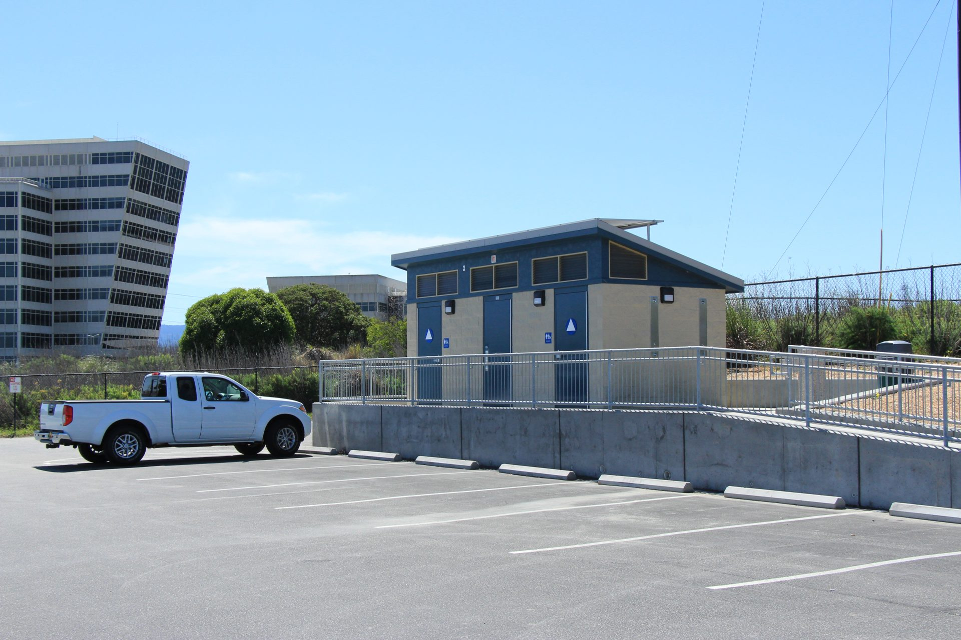 Empty parking lot with ramp up to building with bathrooms