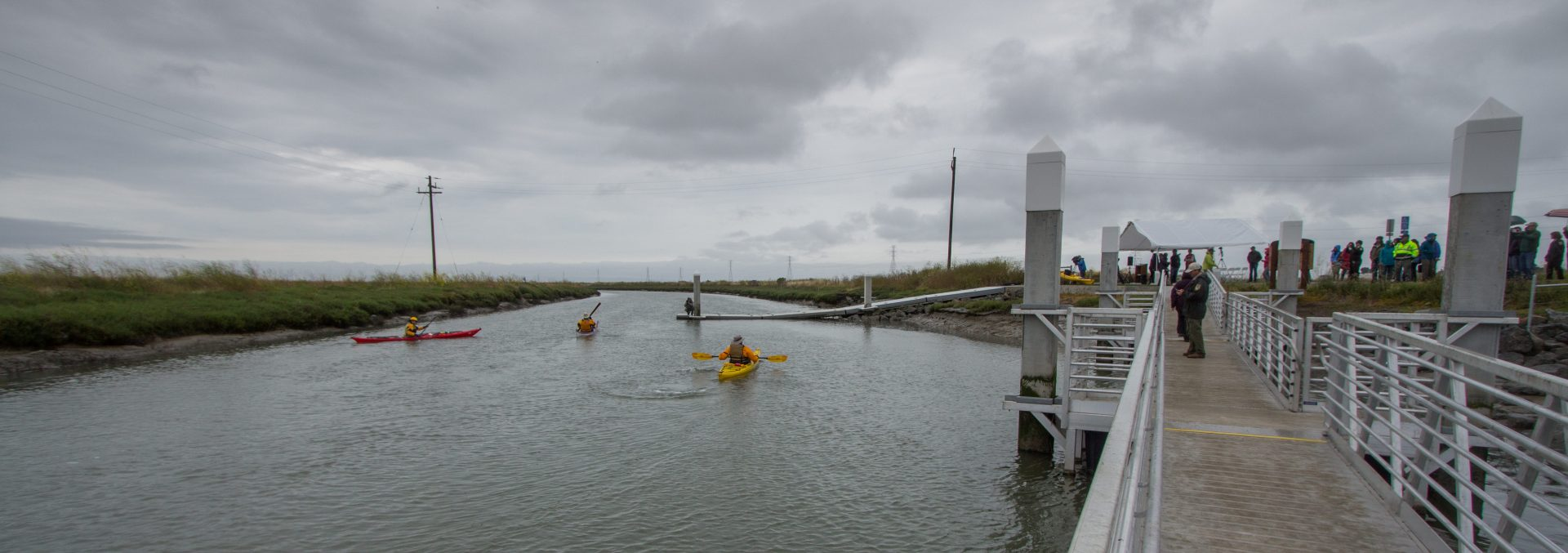 Kayakers on left in water, with people on piers and dock on right
