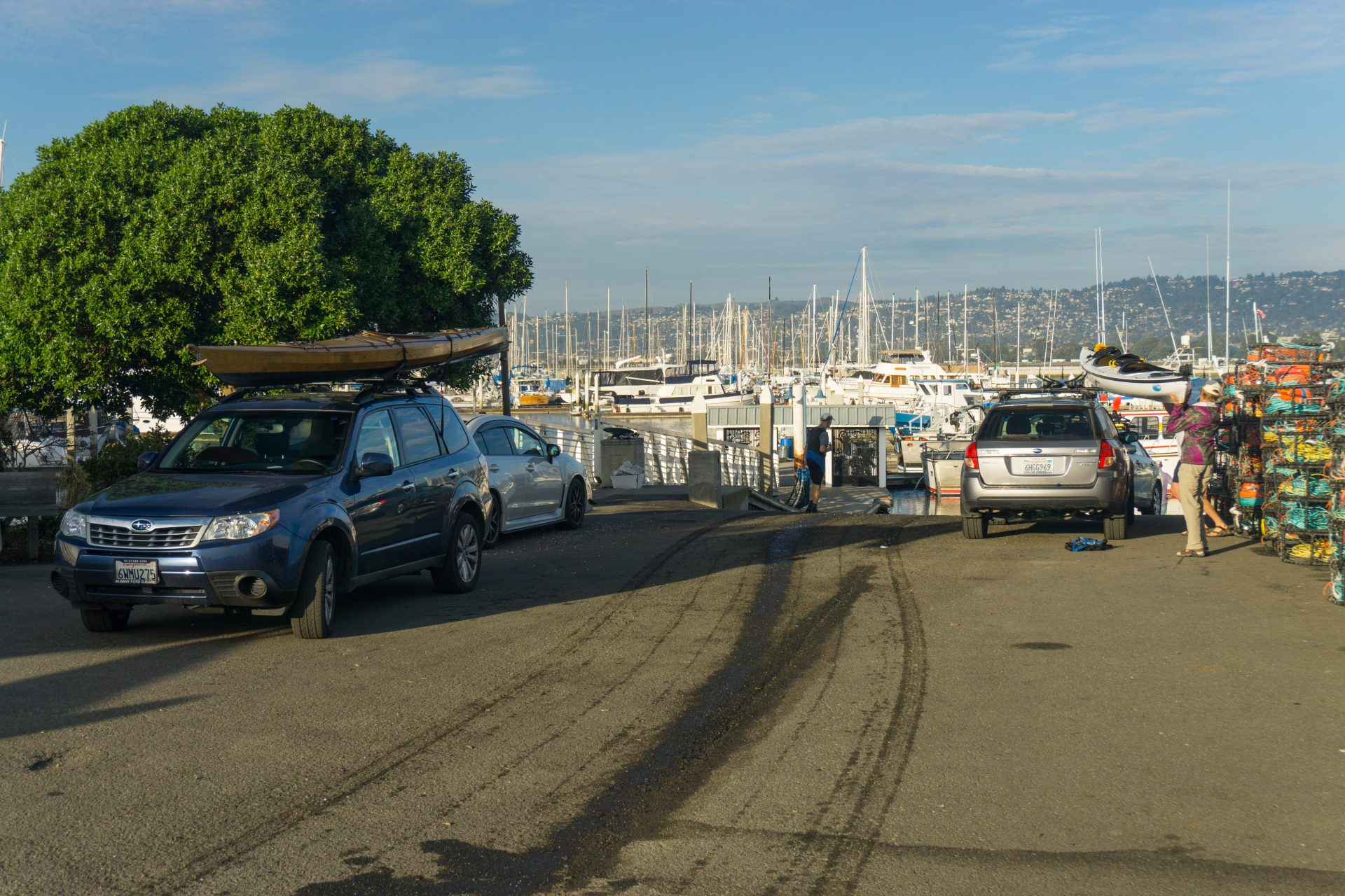 two Subaru station wagons with kayaks on top, next to boat ramp entrance, with boats in a marina in the distance