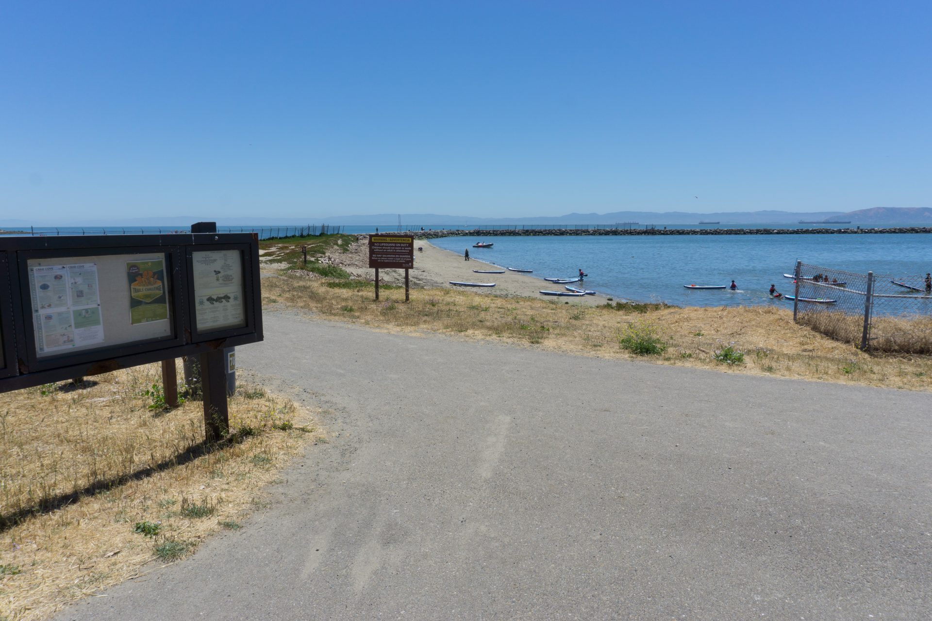 Signage kiosk on left, paved path, water beyond with many paddleboarders