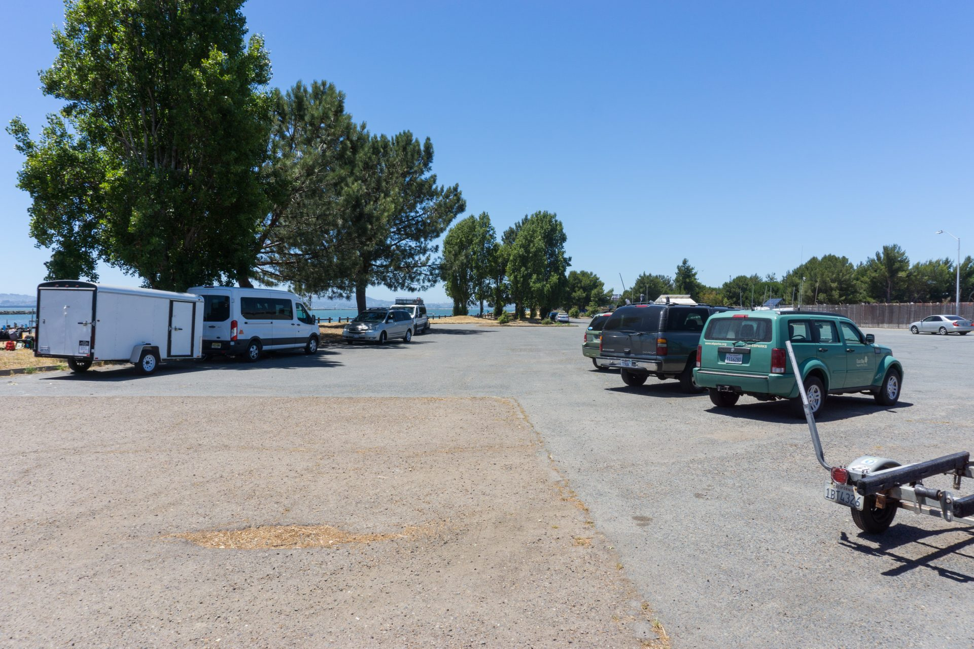 Parking lot with large vans, trailers, surrounded by trees