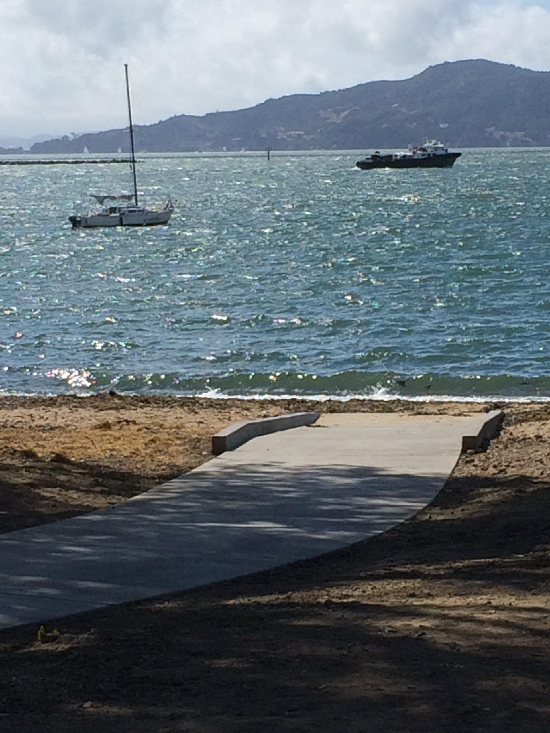 Concrete path curving to sandy beach and bay, sailboat and large ship in distance