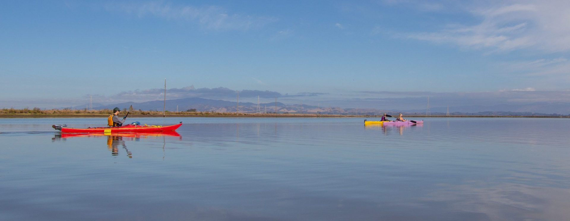 red, yellow, purple kayaks with paddlers headed out