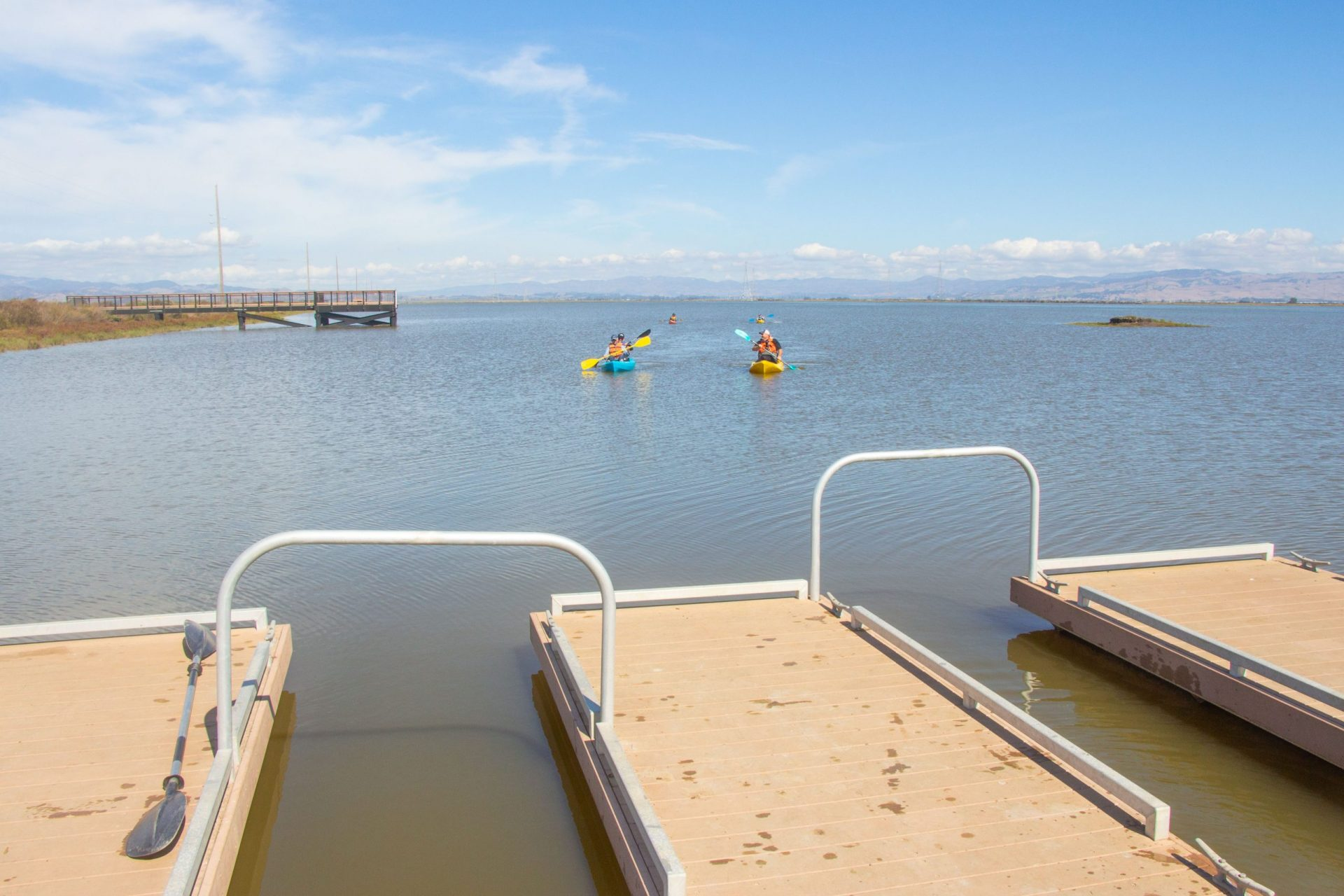Kayakers paddling by piers
