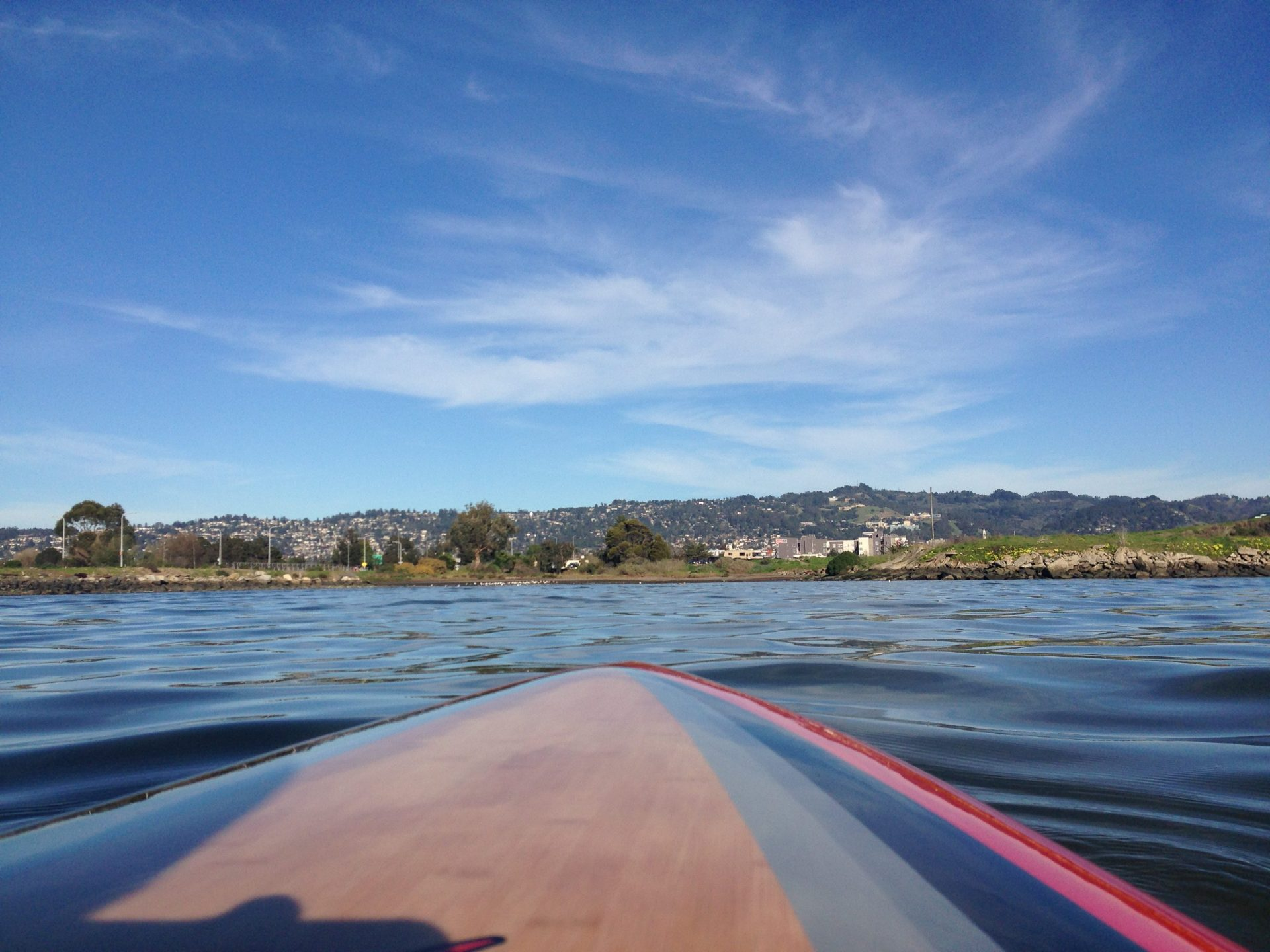 View from paddleboard on water, toward shore and East Bay Hills