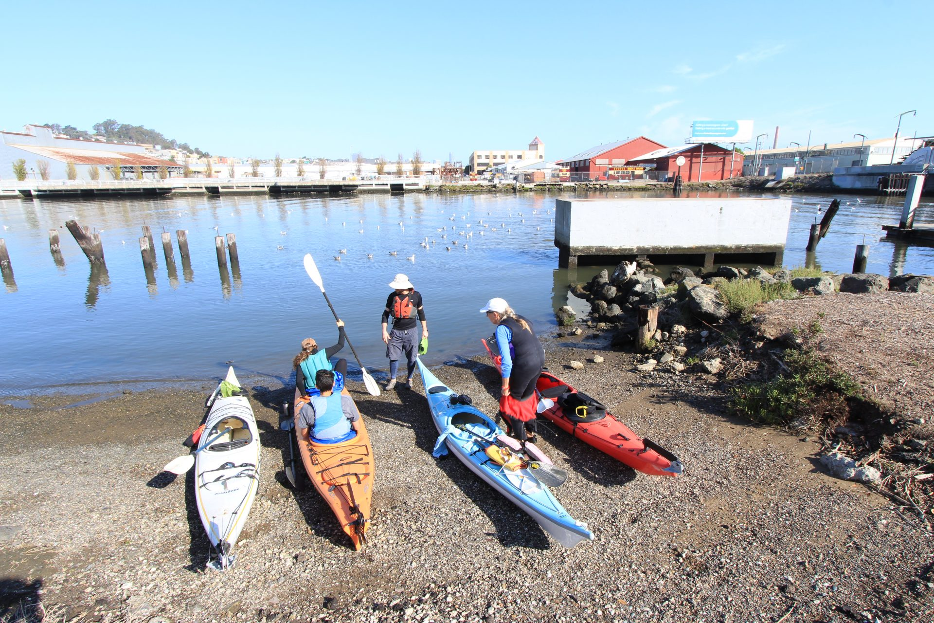 Four kayaks on beach, two people in a double, and two people standing