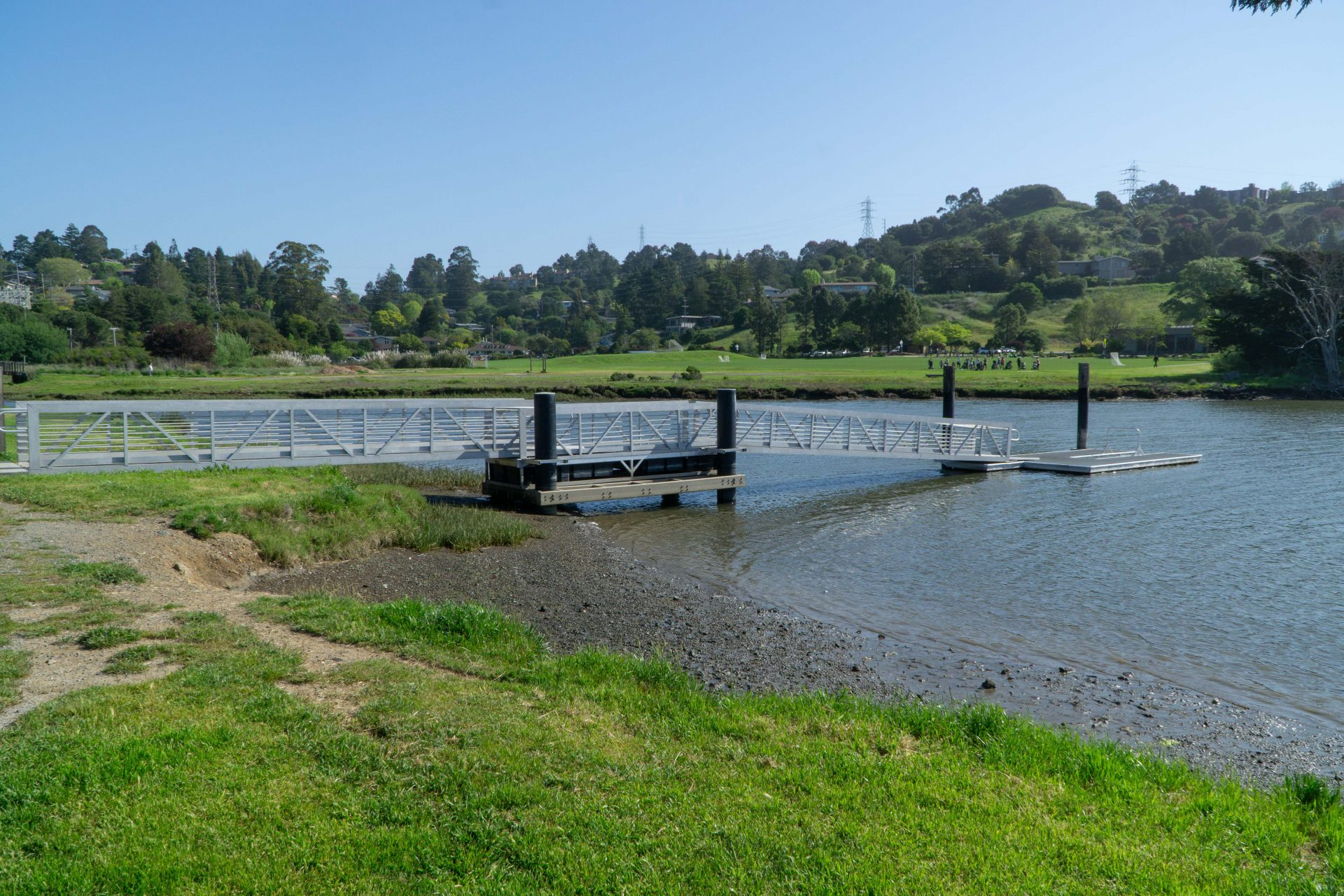 green lawn, muddy shore, ramp to pier