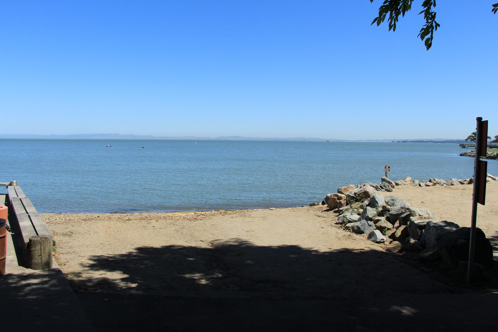 flat sandy beach with concrete wall on let and riprap on right