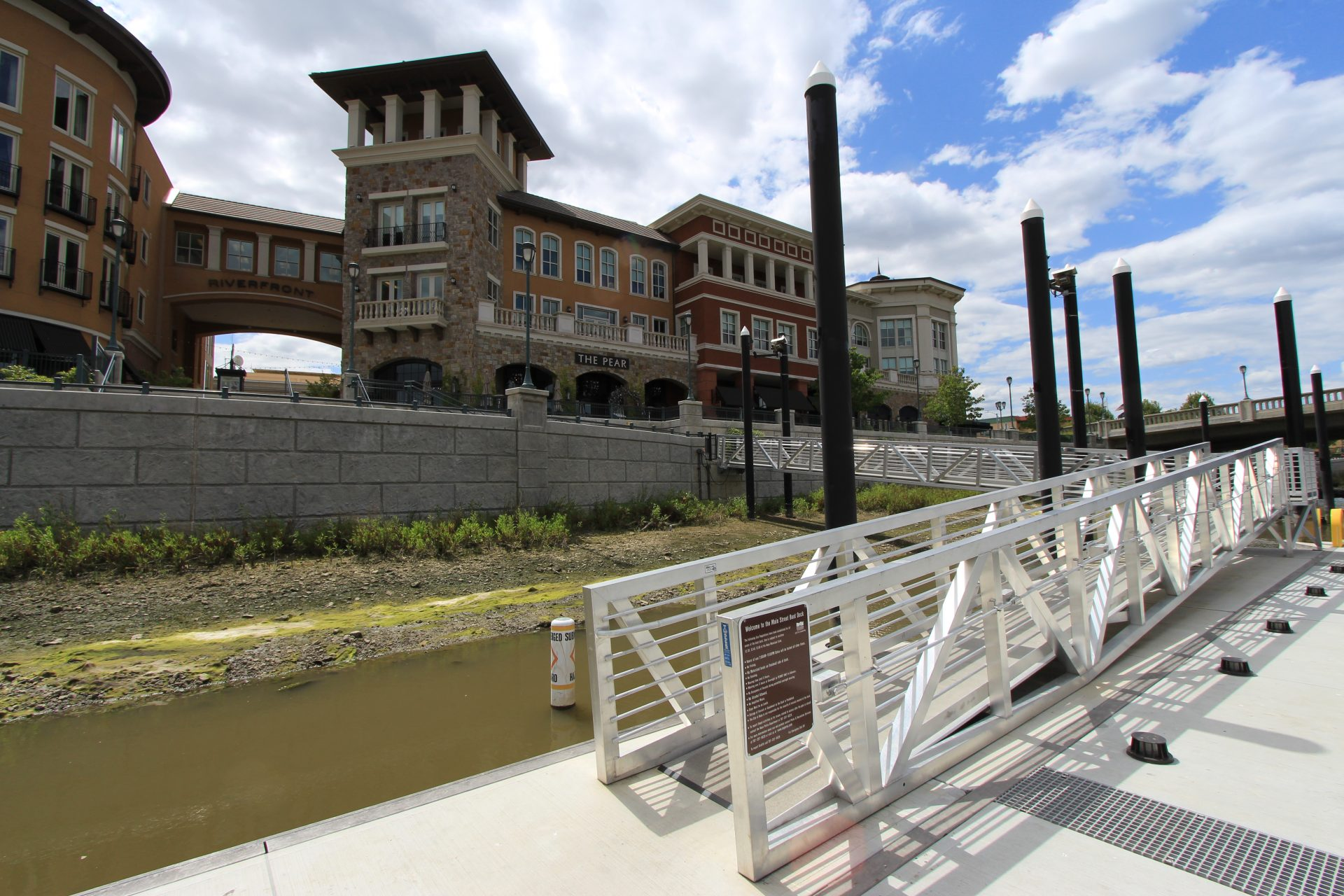 View of ramp to shore, retaining wall, riverfront buildings