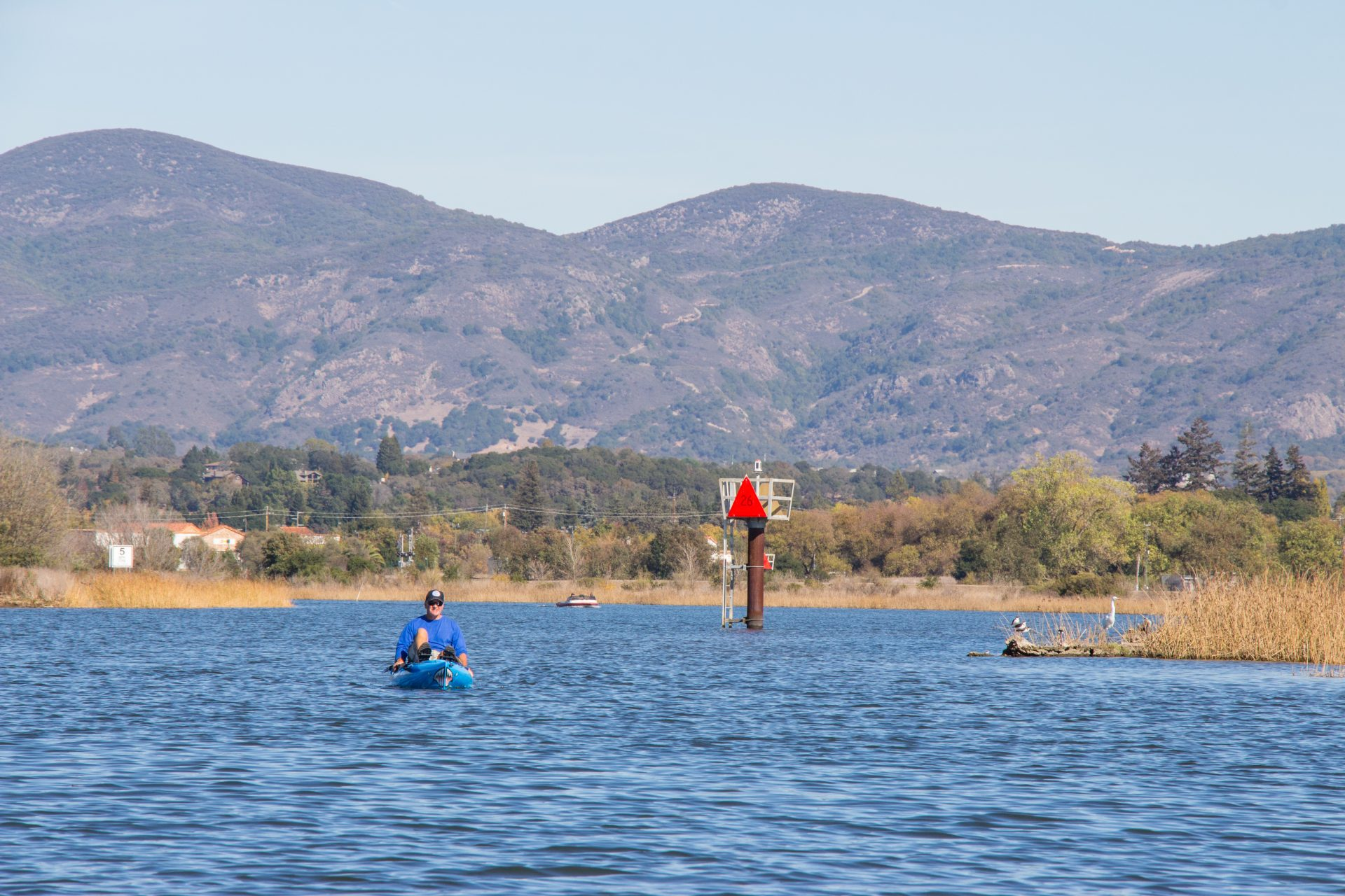 brown hills over blue waters, with loan kayaker paddling toward the camera