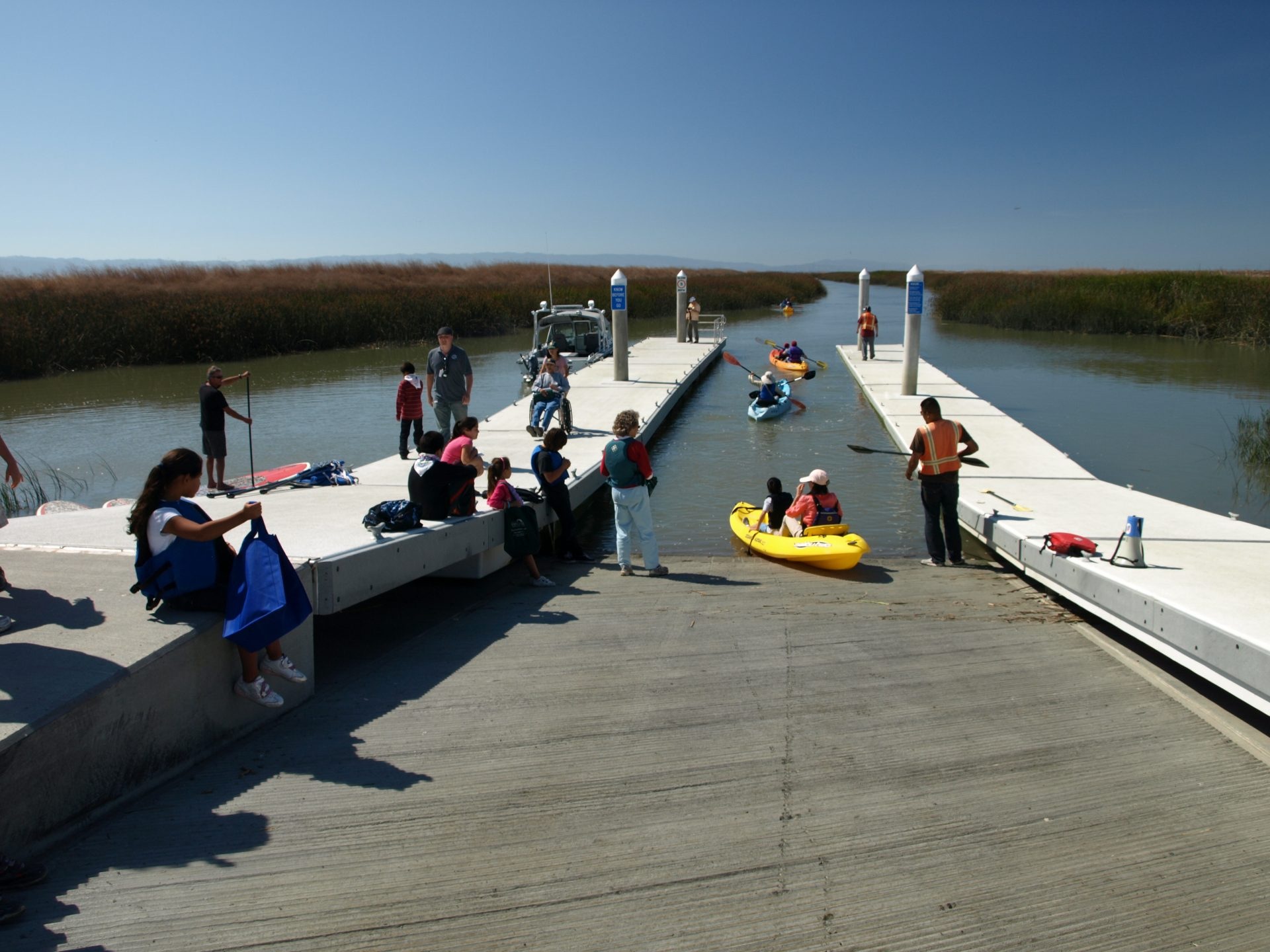 People of many ages standing on dock and in water, some paddling kayaks off boat ramp