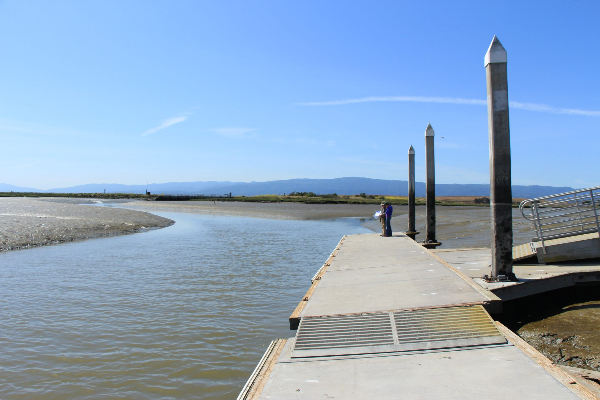 People at far end of floating dock in a narrow channel with mudflats exposed at low tide