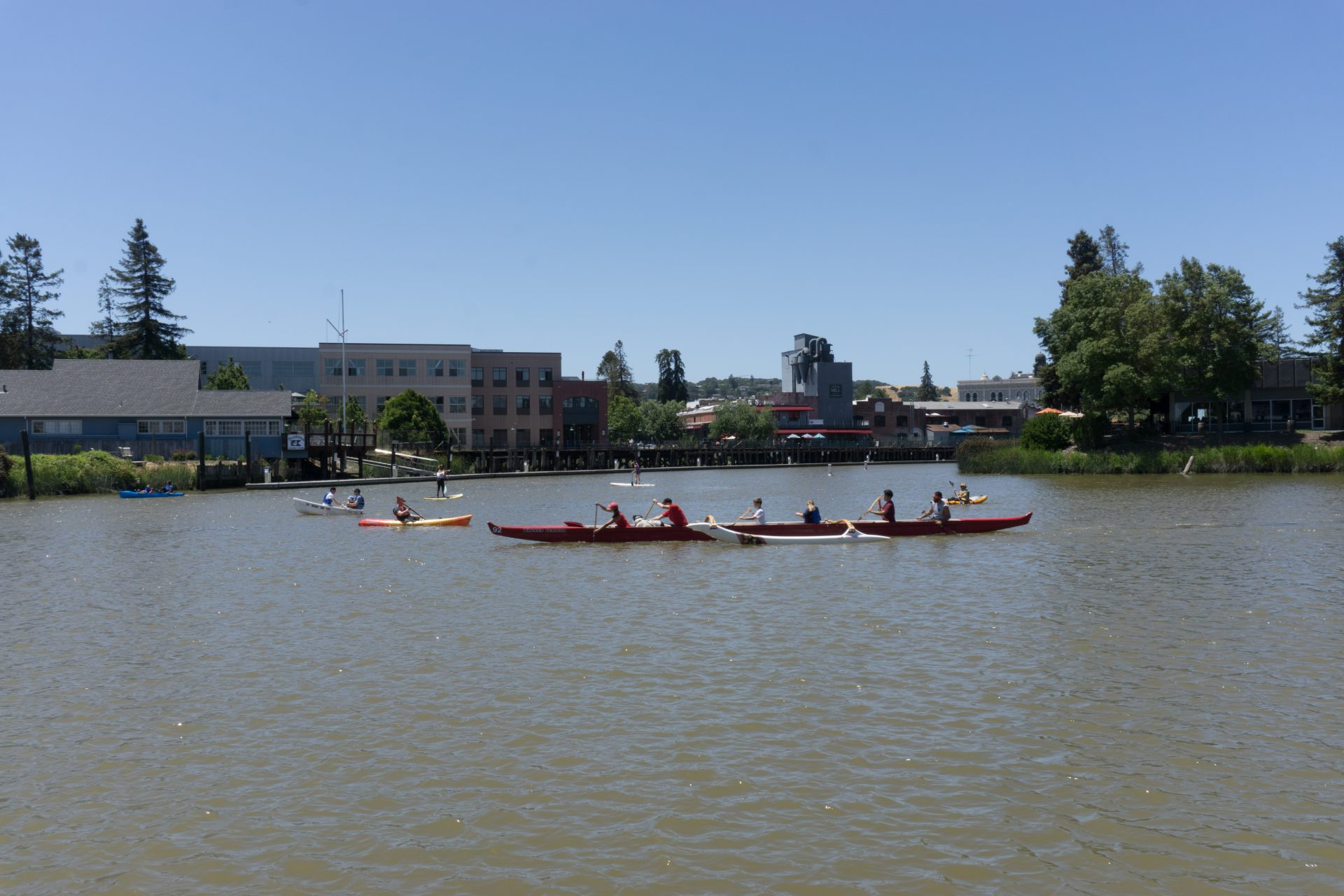 Paddlers in a long outrigger canoe, with kayakers and standup paddlers nearby
