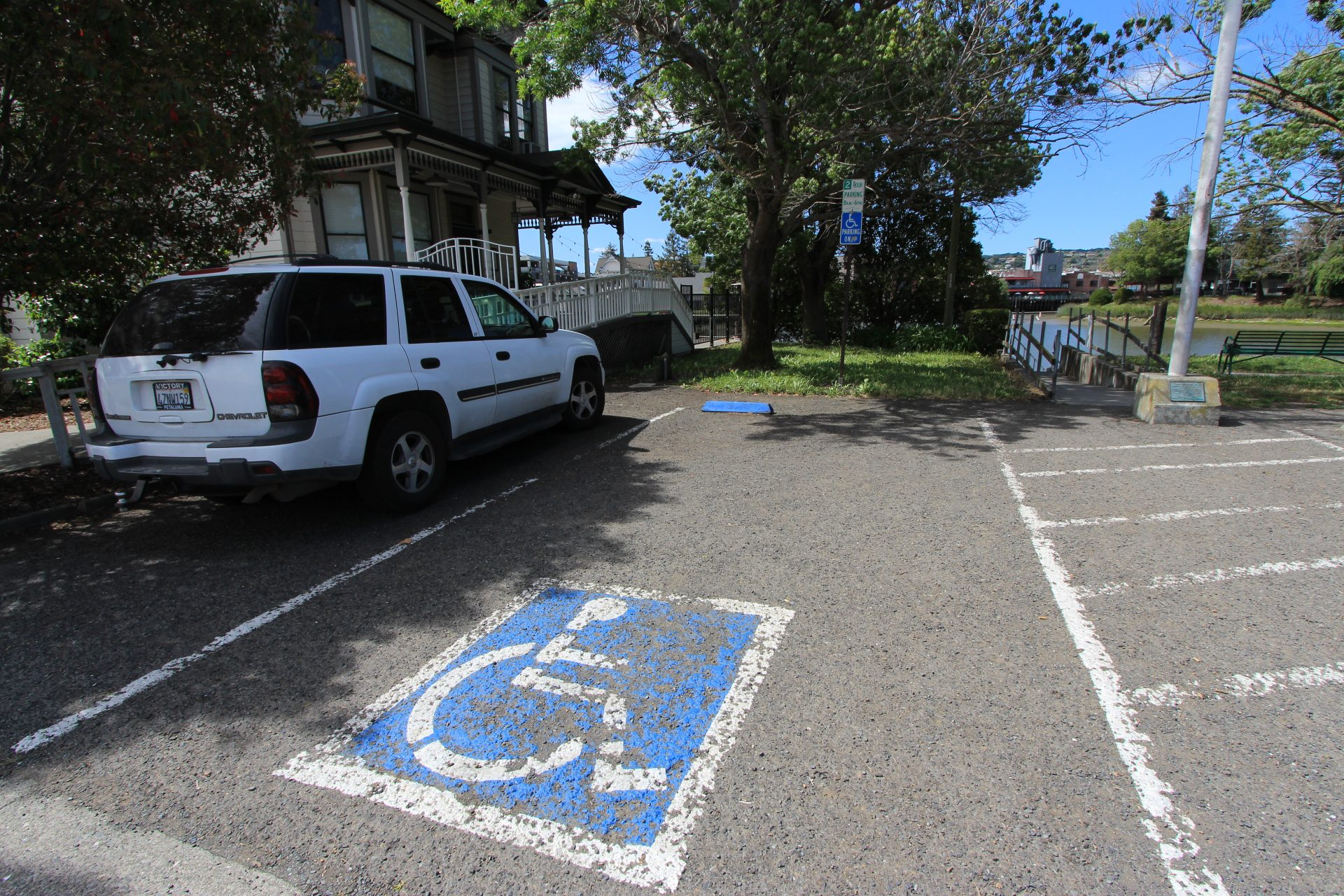 Handicap accessible parking spot, with white SUV on left