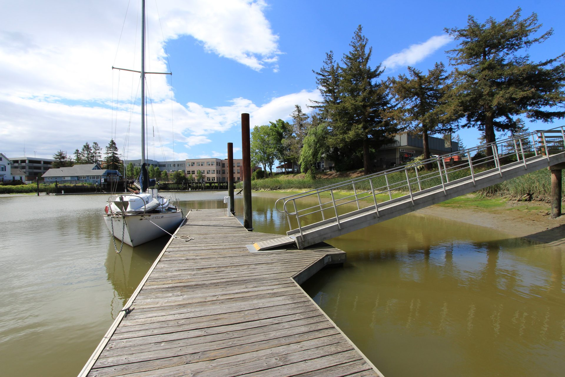ramp down to dock, with small sailboat moored to dock