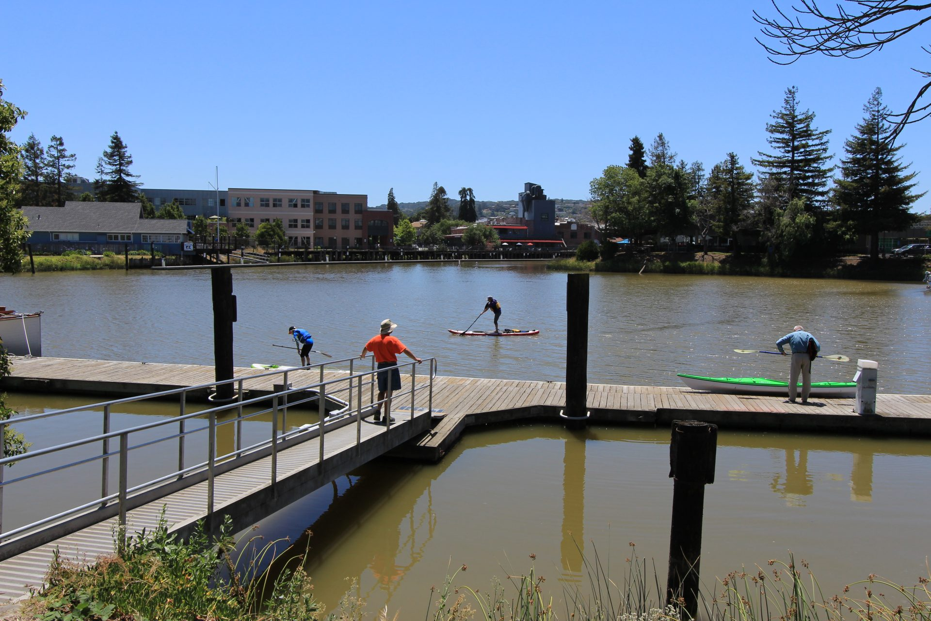 Person standing on ramp down to dock while a kayaker gets ready and a standup paddler passes by