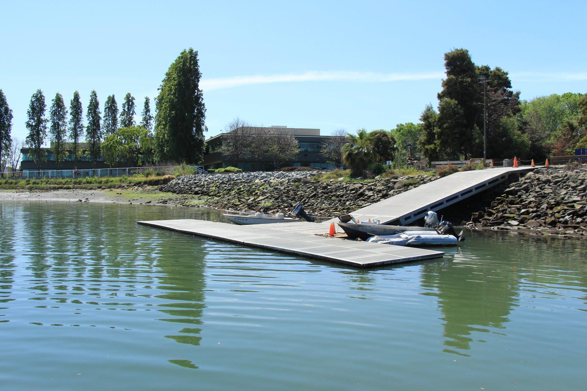 Floating dock with small motorboat, and ramp back up to shore