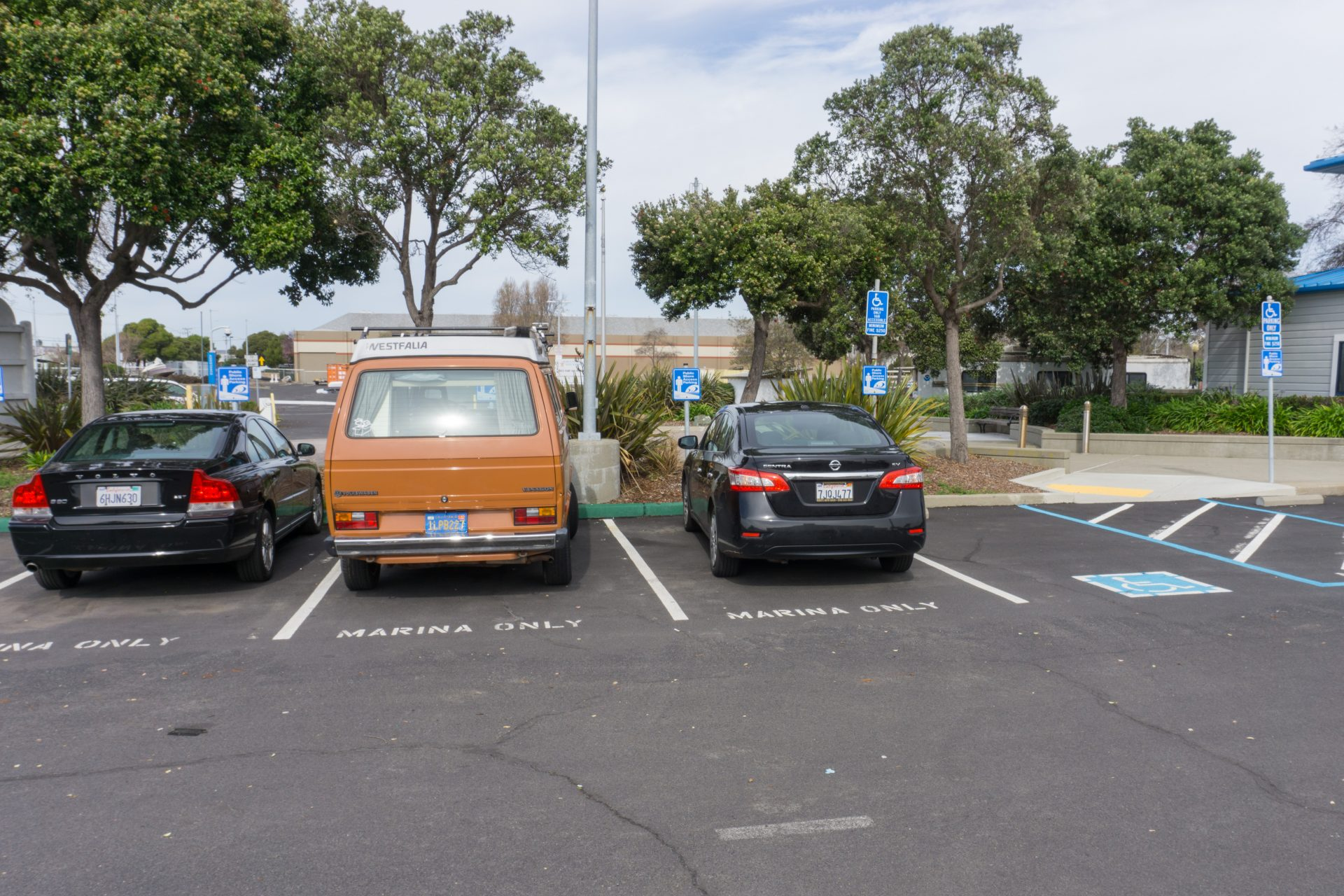 PArking lot with three cars and two open accessible spots