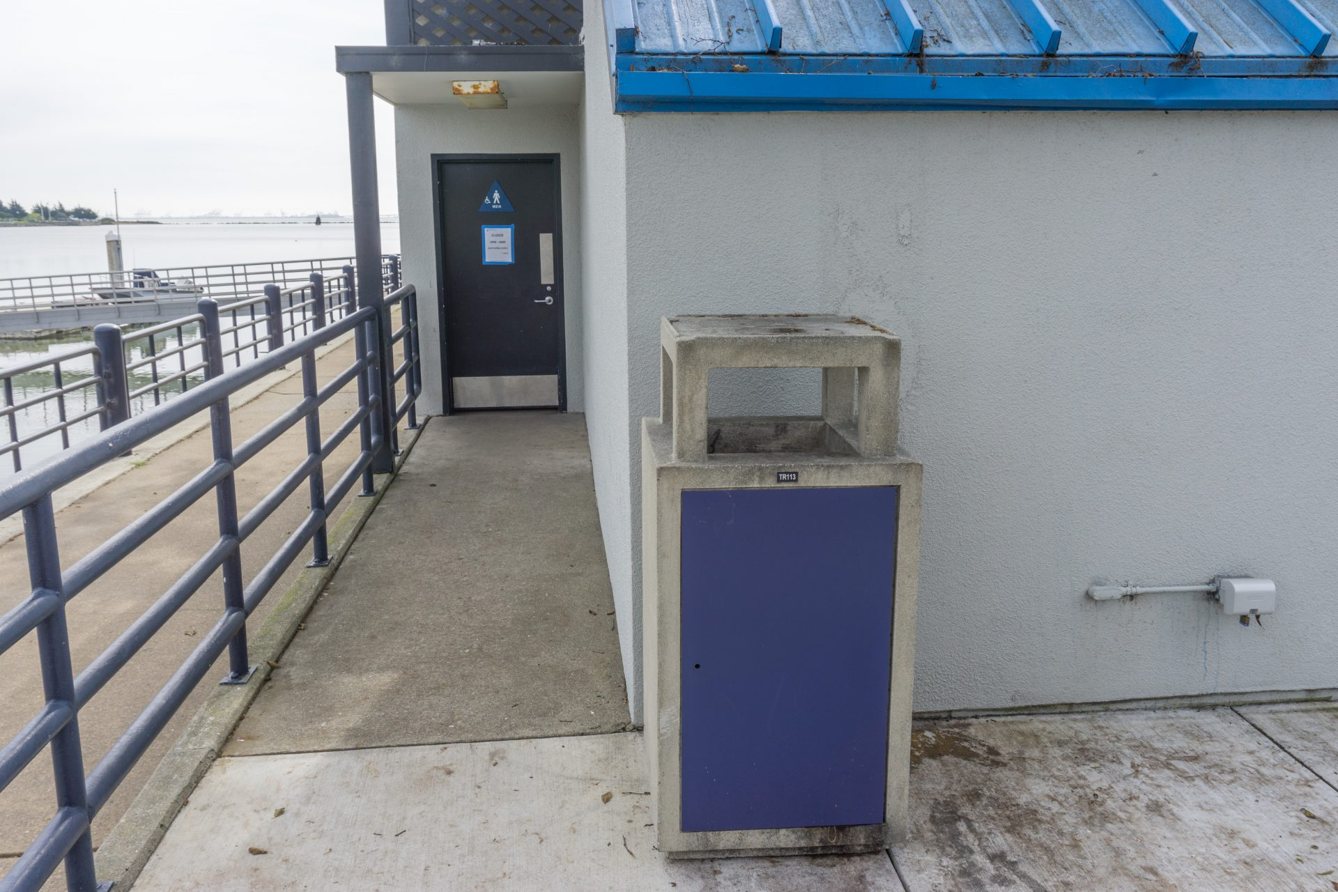trashcan next to stucco building with bathroom