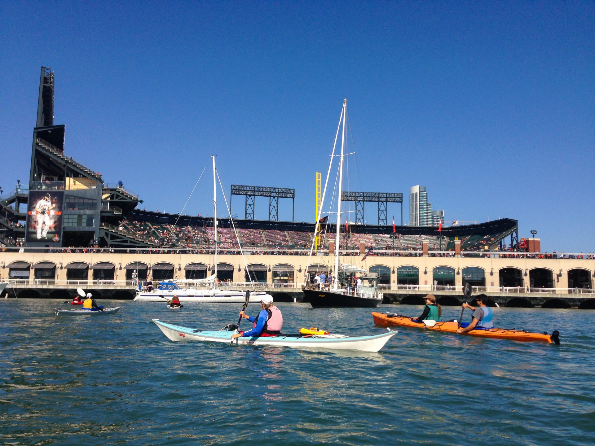 Kayakers and sailboats in front of Giants ballpark