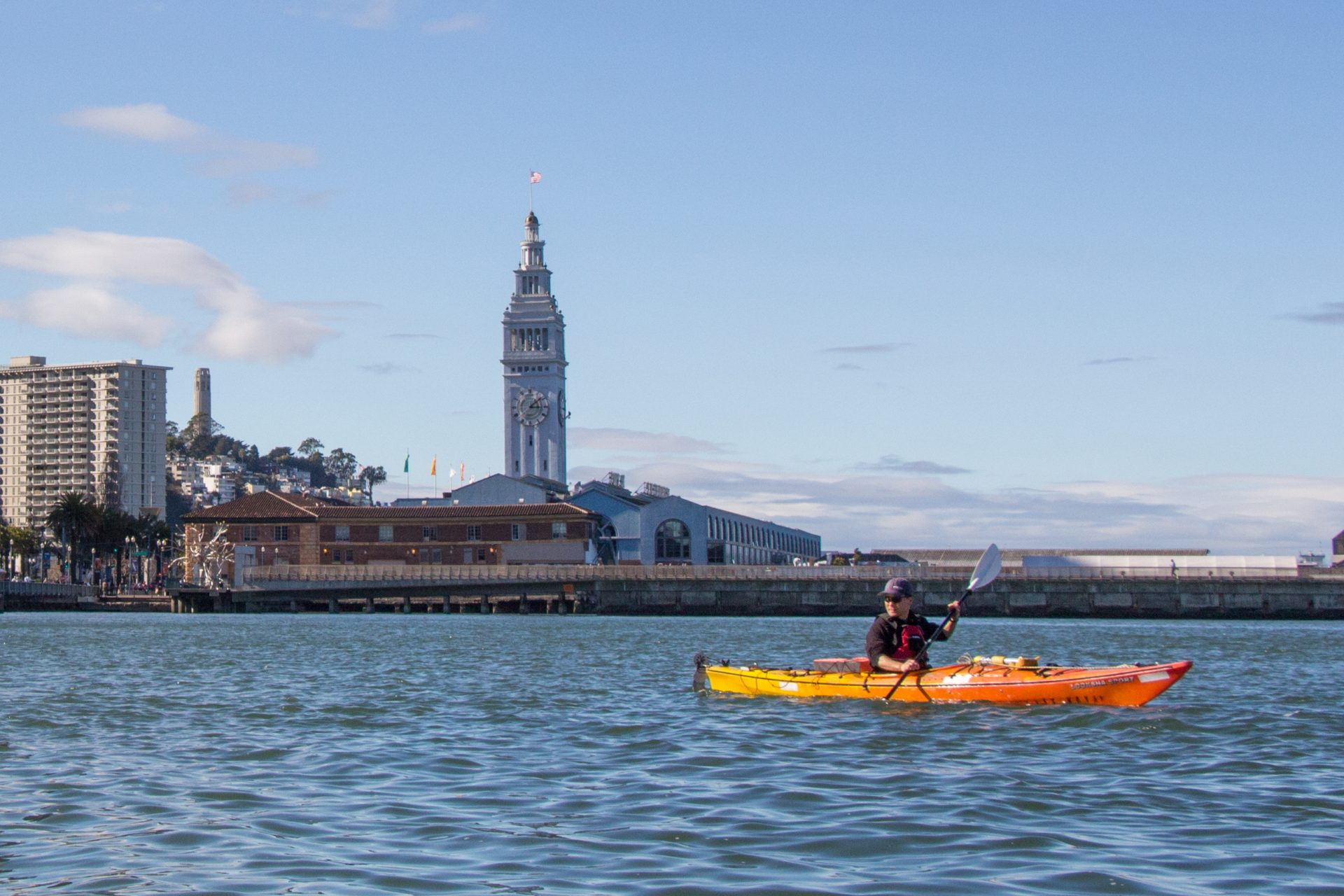 Paddler on the water with Ferry plaza clocktower in distance