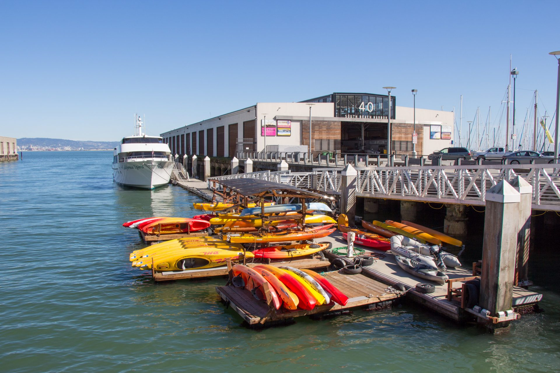 Floating docks with racks full of densely packed kayaks, Pier 40 in distance