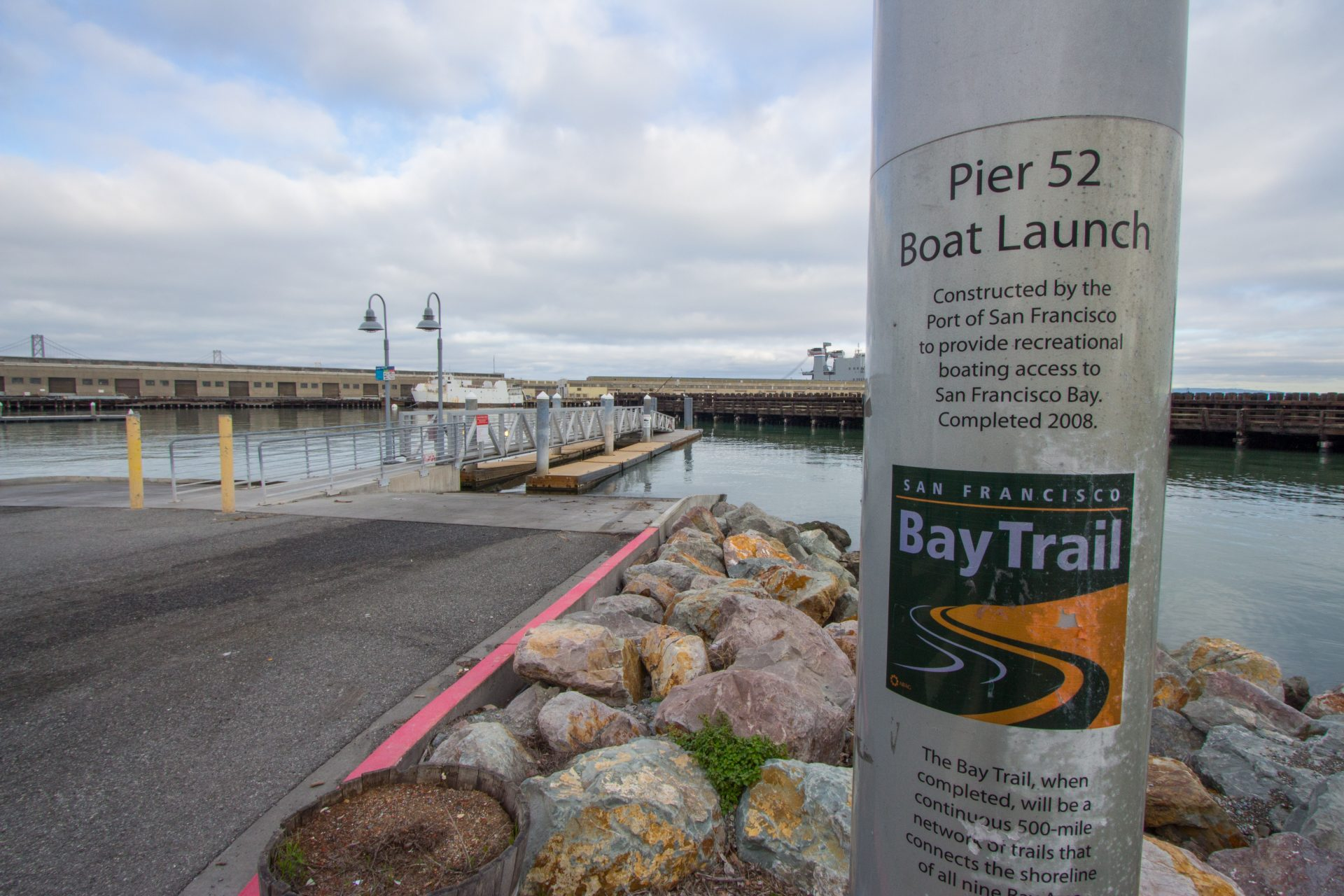 Sign printed on round post: Pier 52 Boat Launch: Constructed by the Port of San Francisco to provide recreational boating access to San Francisco Bay. Completed in 2008.