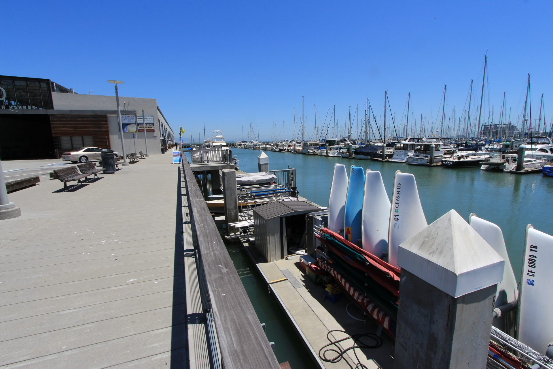 Wide boardwalk on left, dock below on right with small sailboats lined up vertically in storage