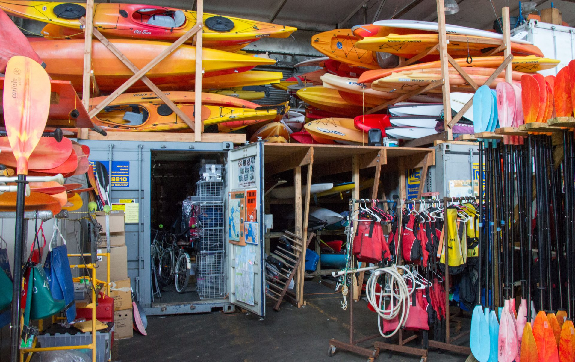 Shed very full of many orange kayaks, life jackets, paddles, and other equipement
