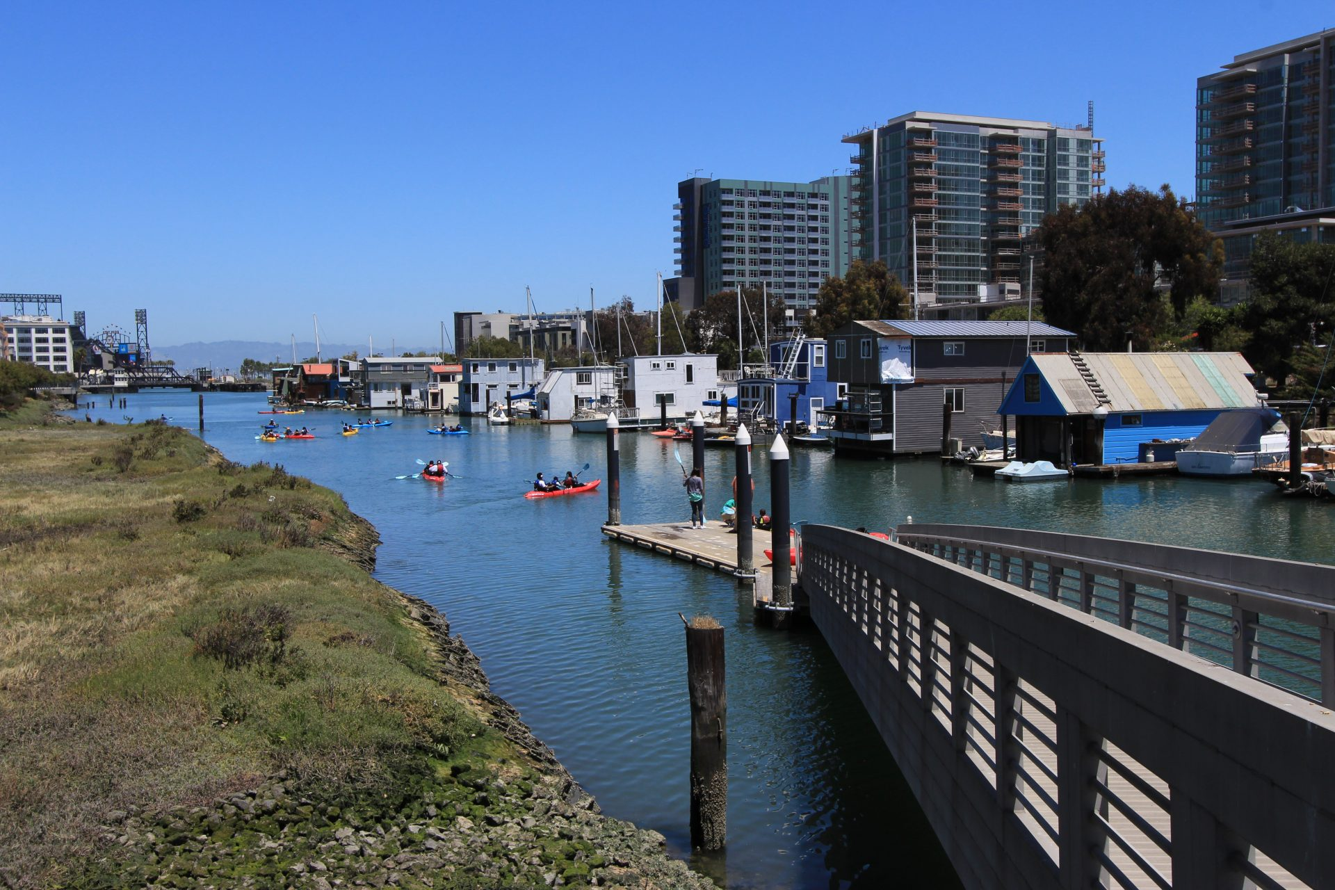 Narrow channel with many color kayaks, and grassy meadow on left and houseboats on right. A ramp descends to a floating dock
