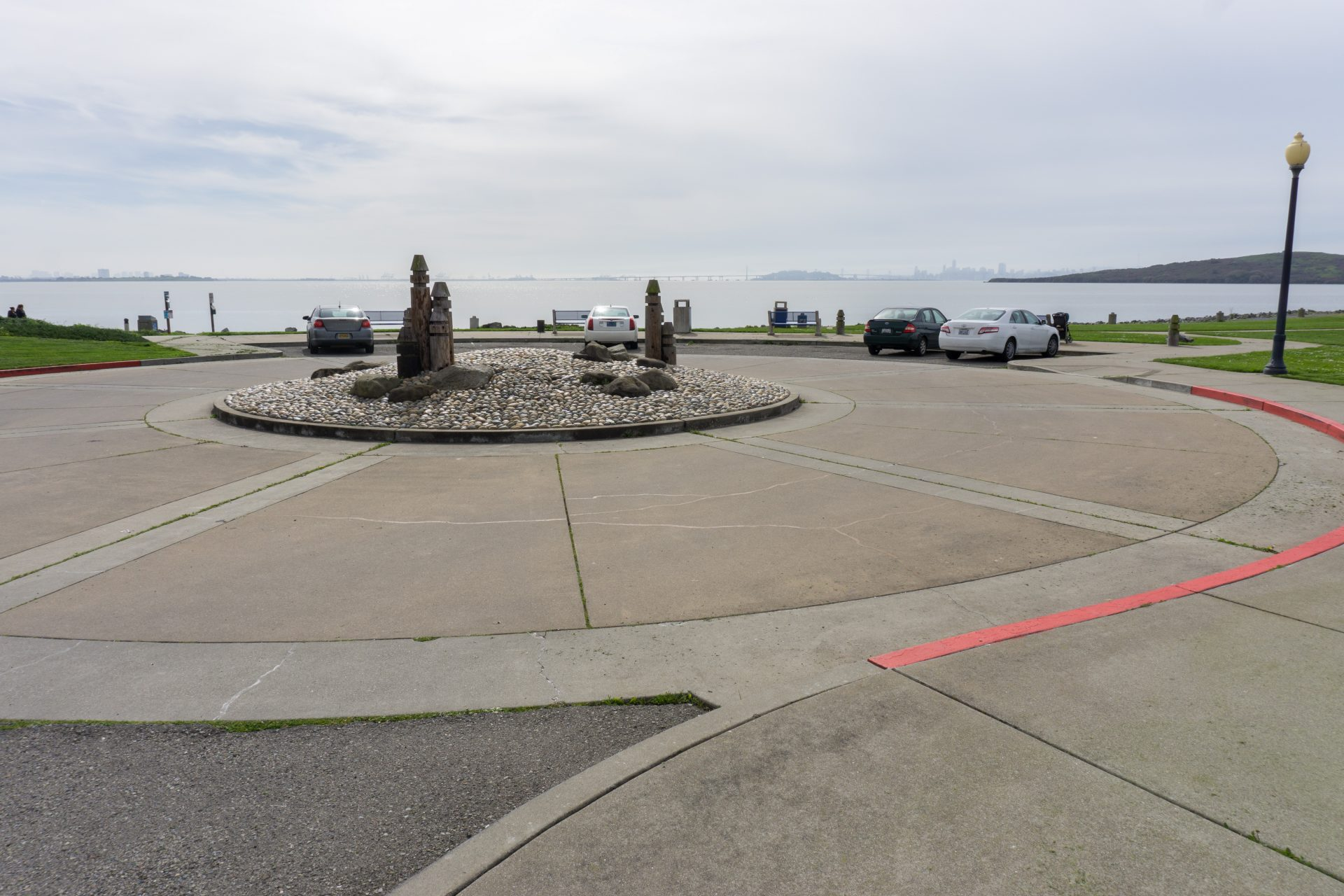 Roundabout paved driveway with wood and concrete sculptures in center
