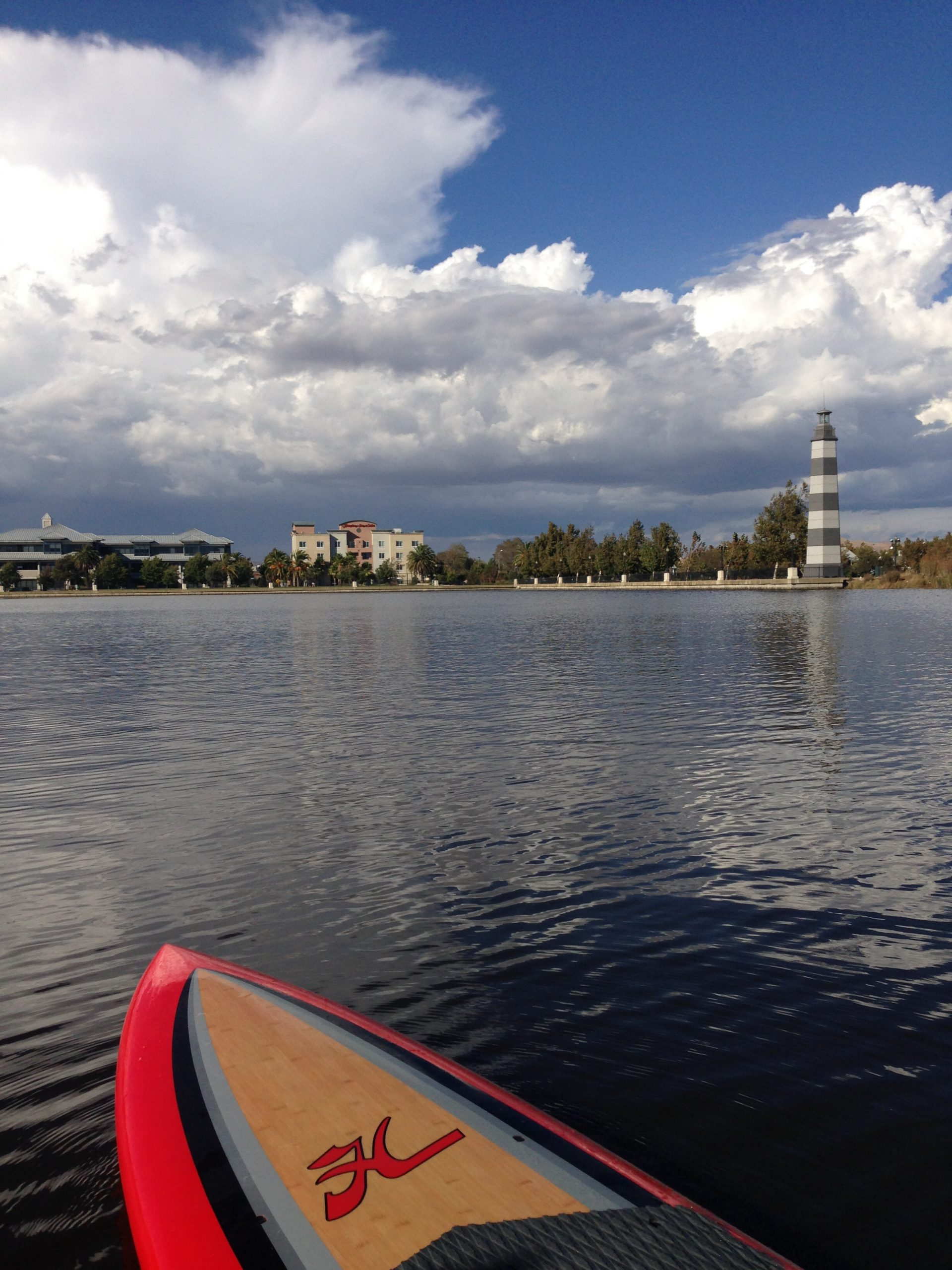 View from paddleboard across water to clouds and sky