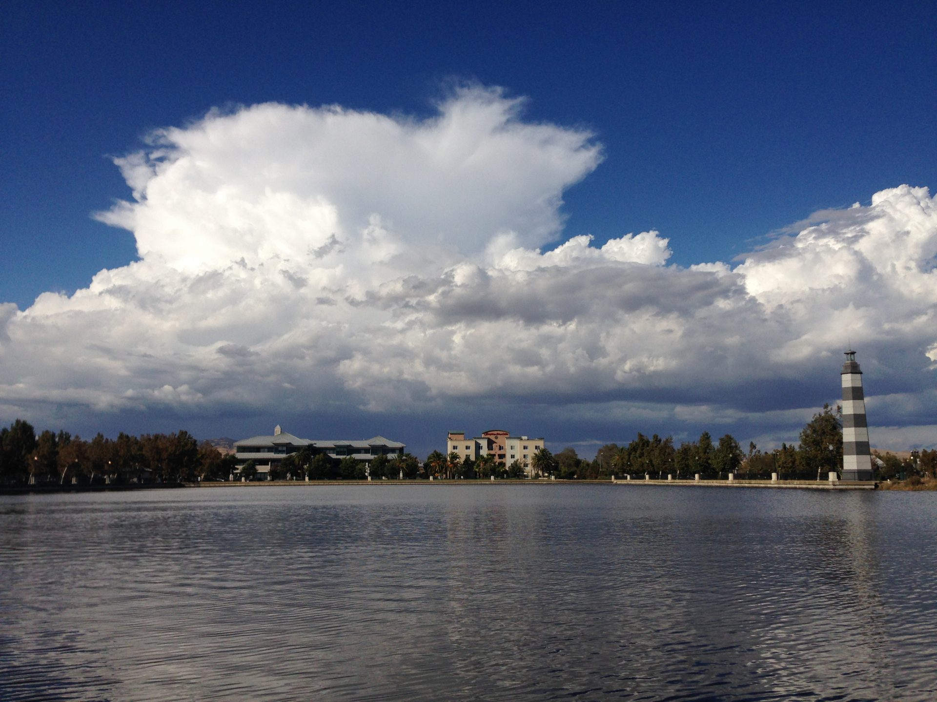 Looking across water to dramatic clouds in blue sky