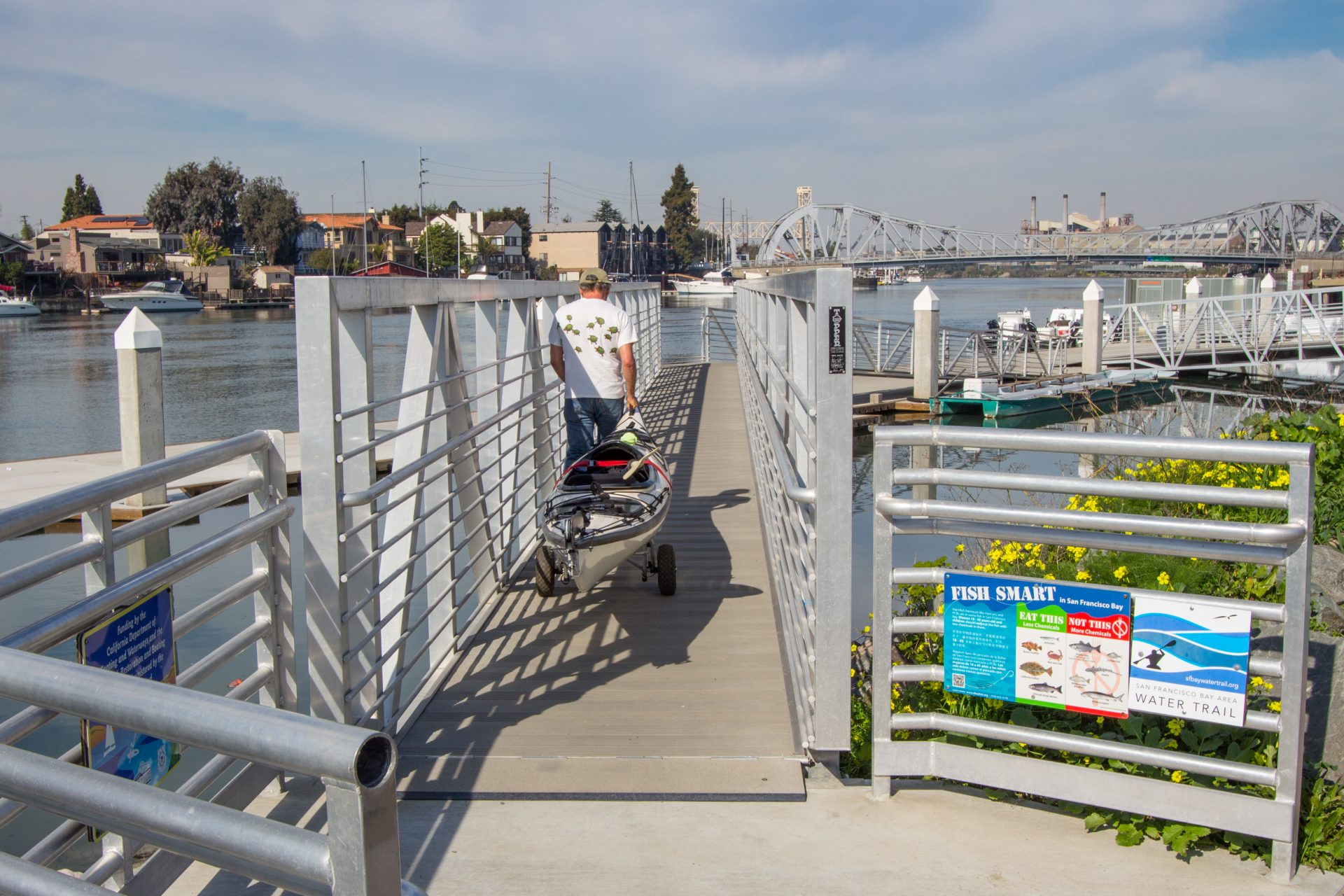 Person pulling kayak on rolling cart down ramp to dock