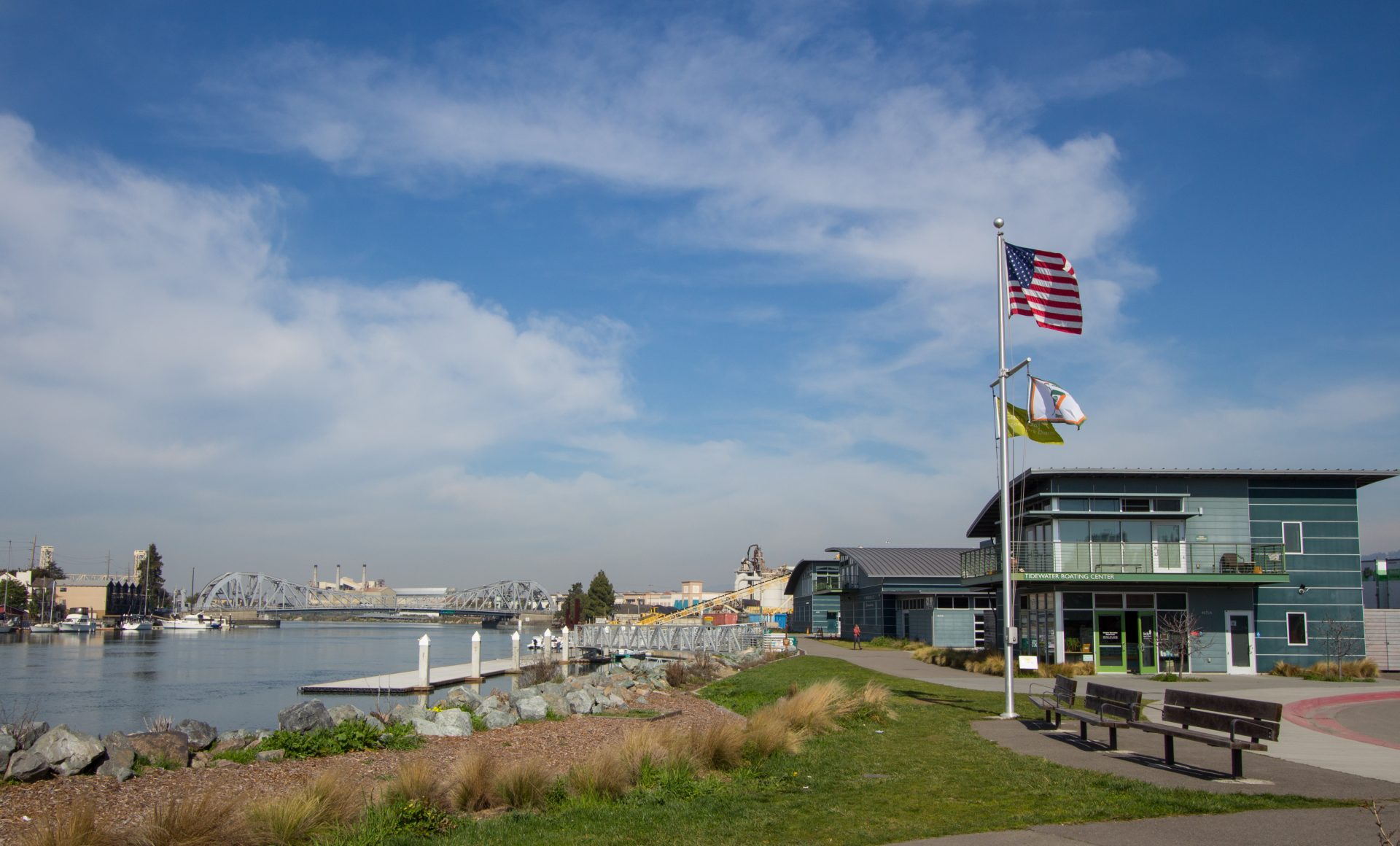 bay on right, green lawn center, flag pole with flags waving in wind. Two-story building in background
