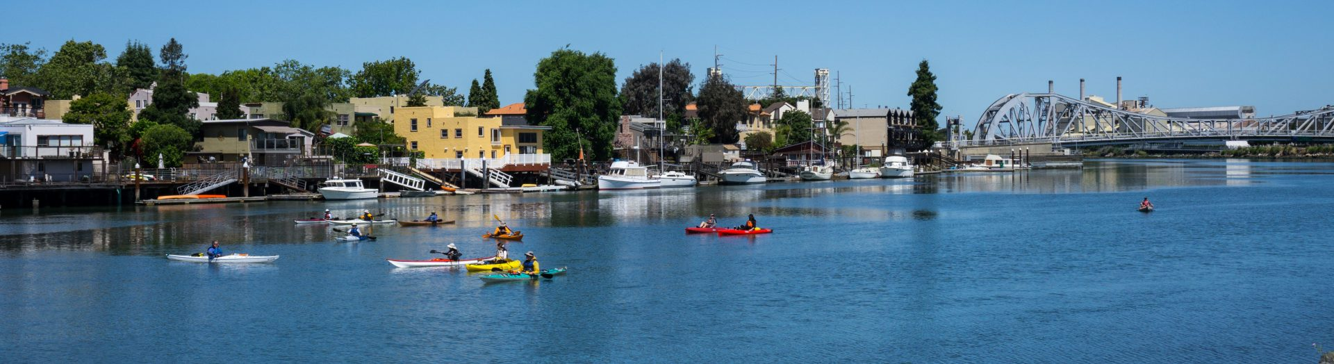 Panoramic view of kayaks on blue water, with shoreline docks and bridge in distance