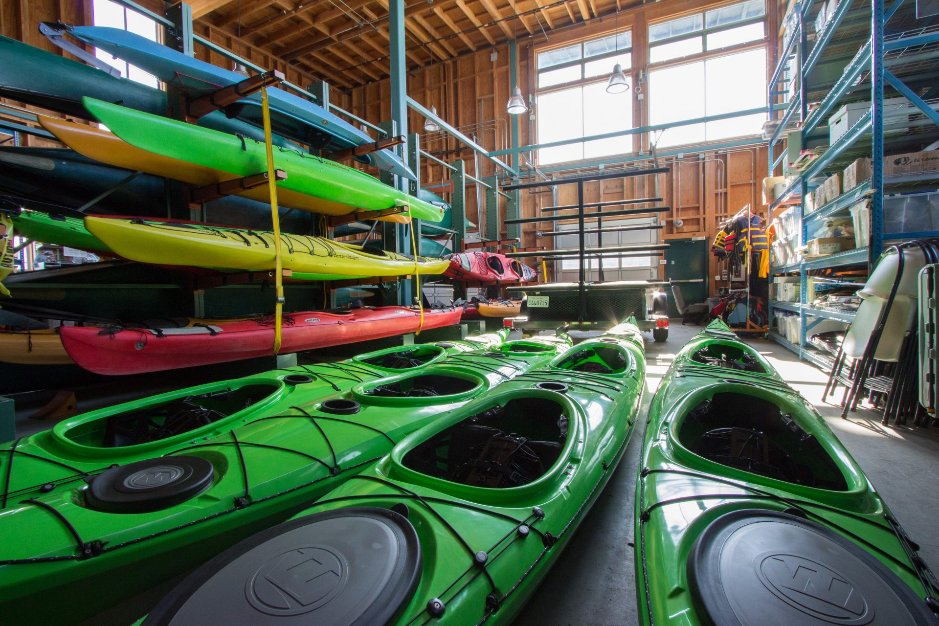 Shed full of double kayaks, on floor and in racks