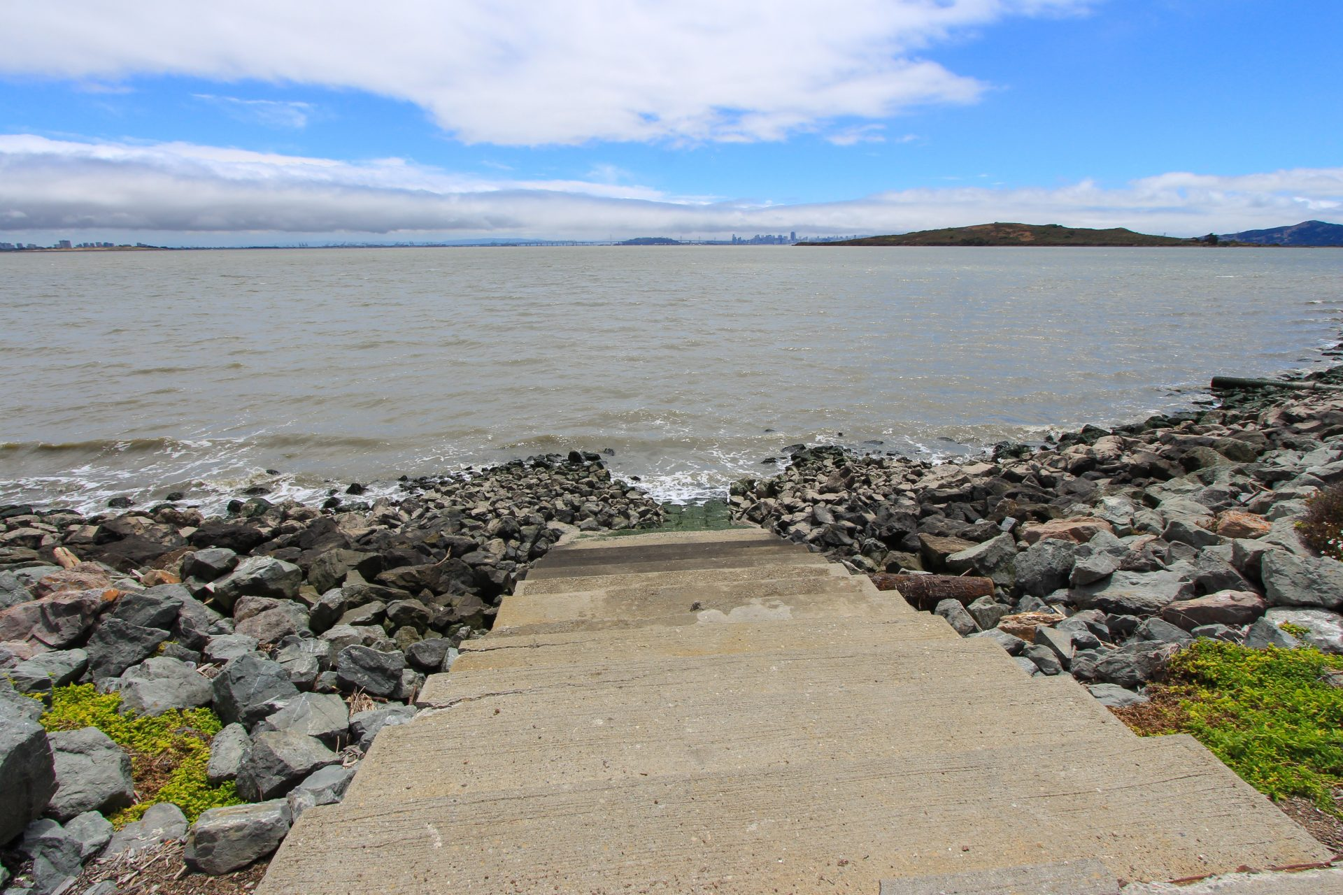 concrete steps descend to water with riprap on both sides